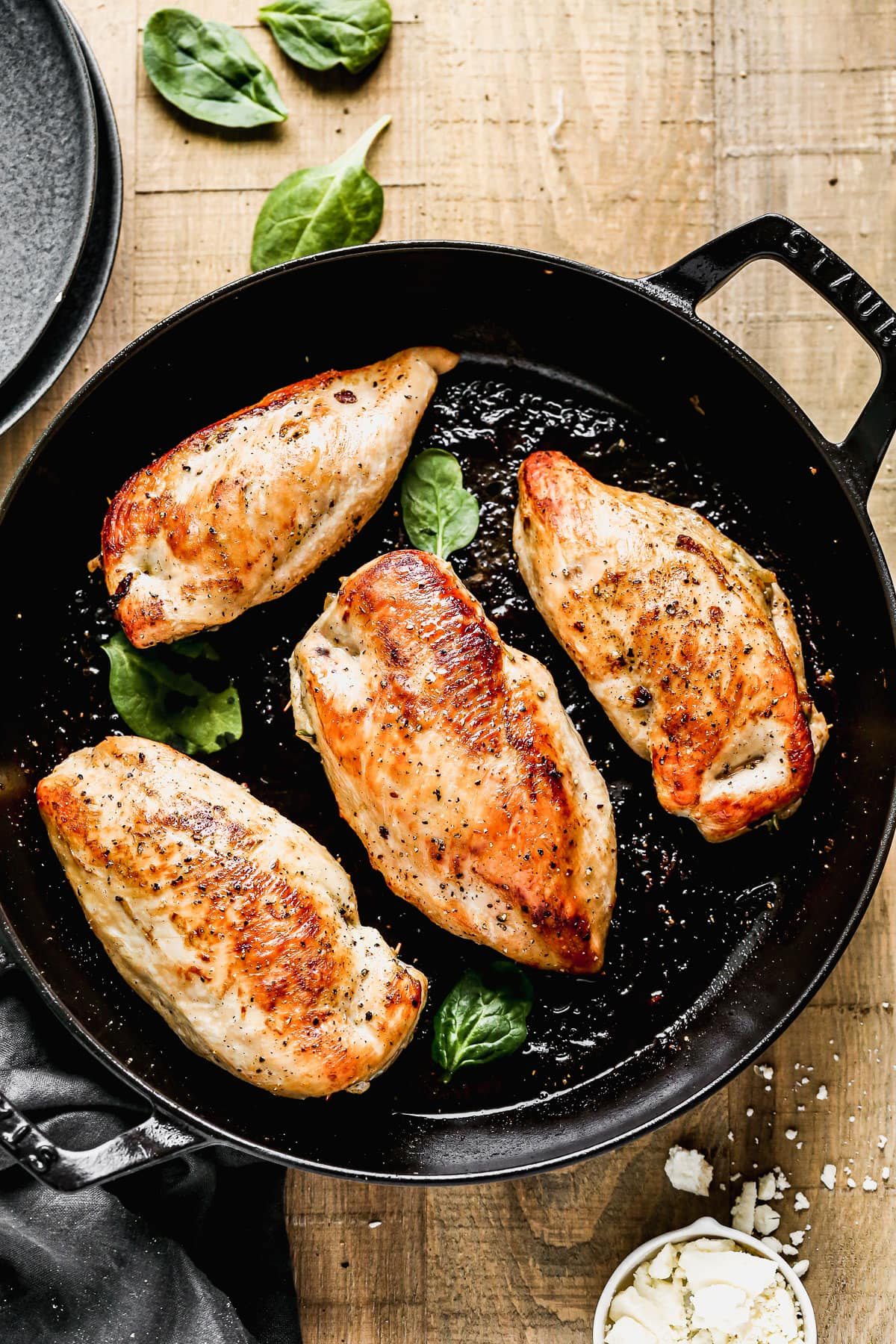 Four spinach stuffed chicken breasts in a skillet