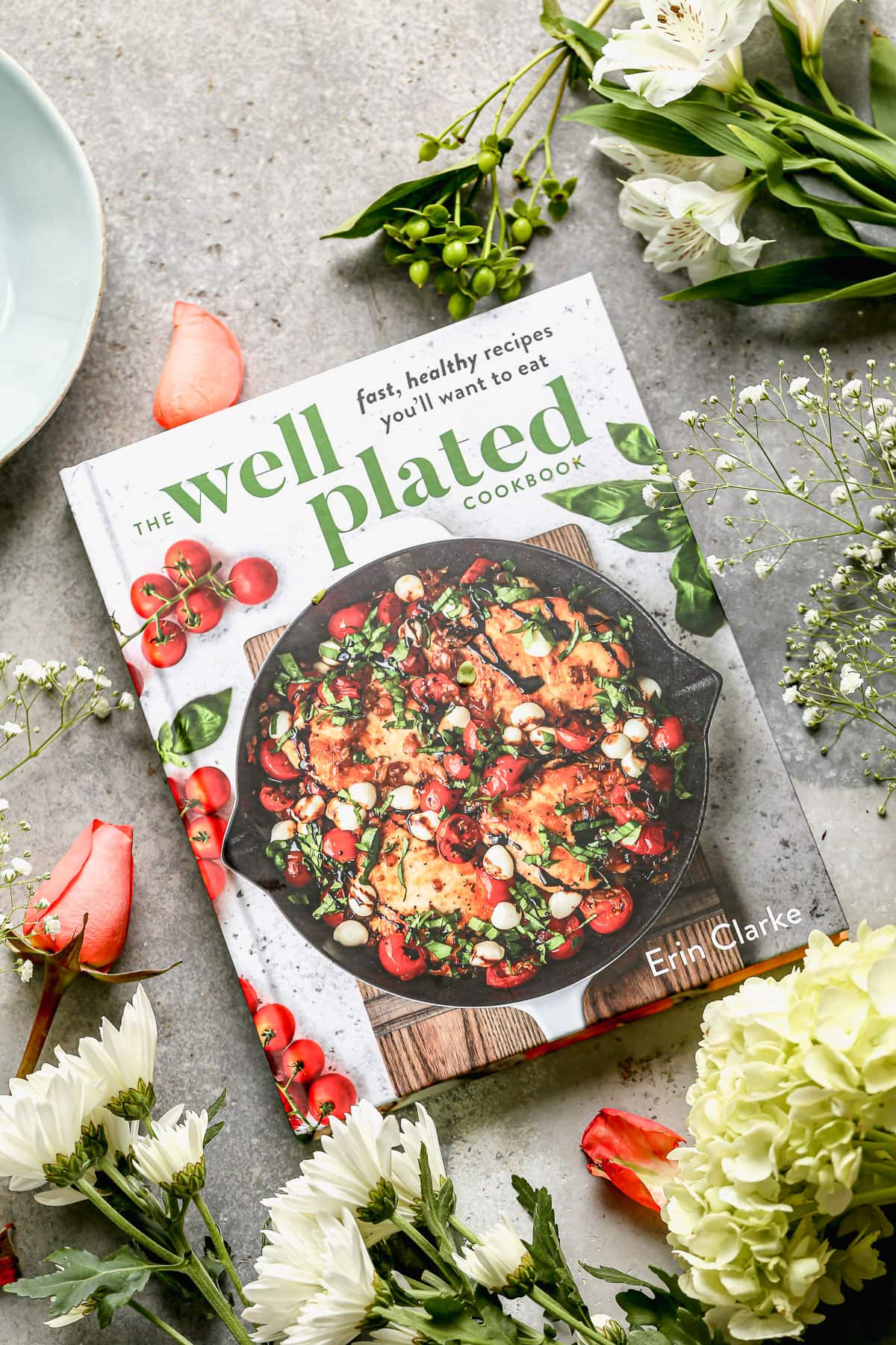 The Well Plated Cookbook surrounded by spring flowers