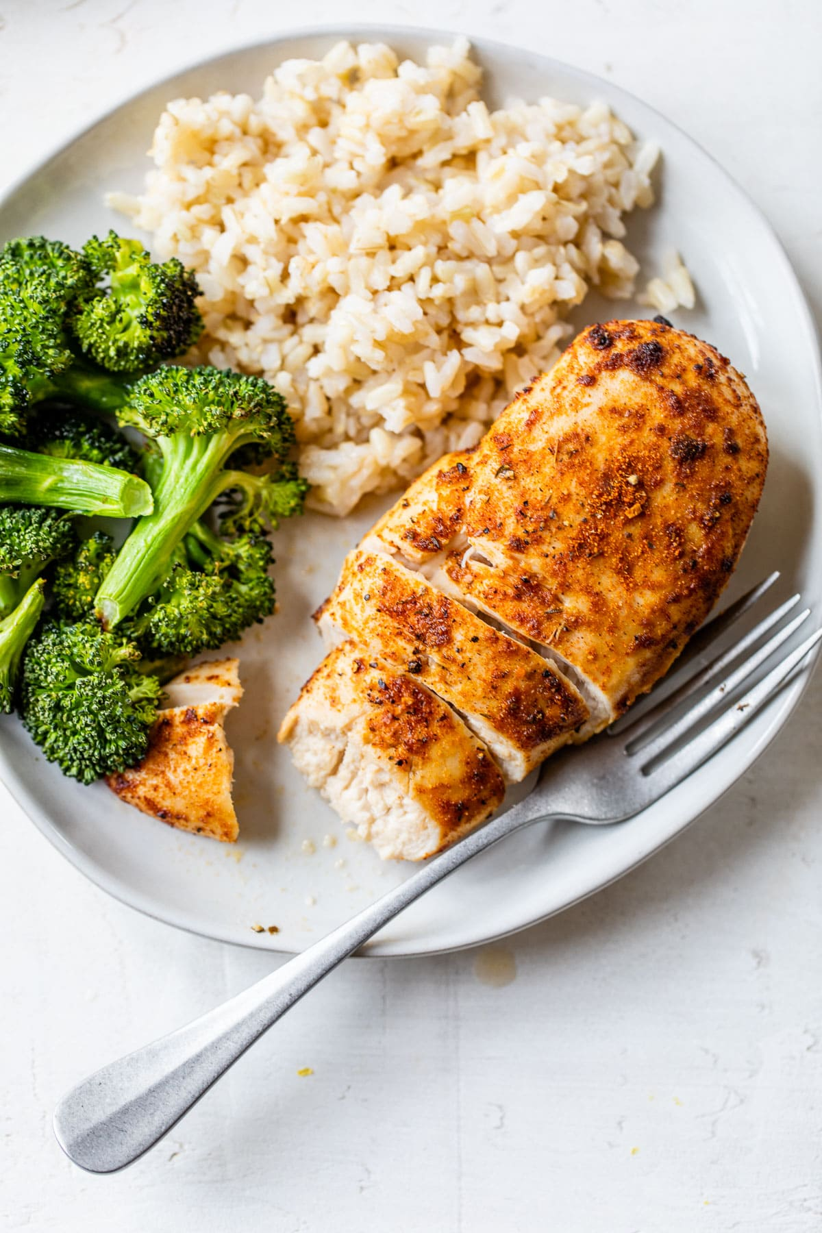 Air fryer chicken breast on a plate with broccoli and rice