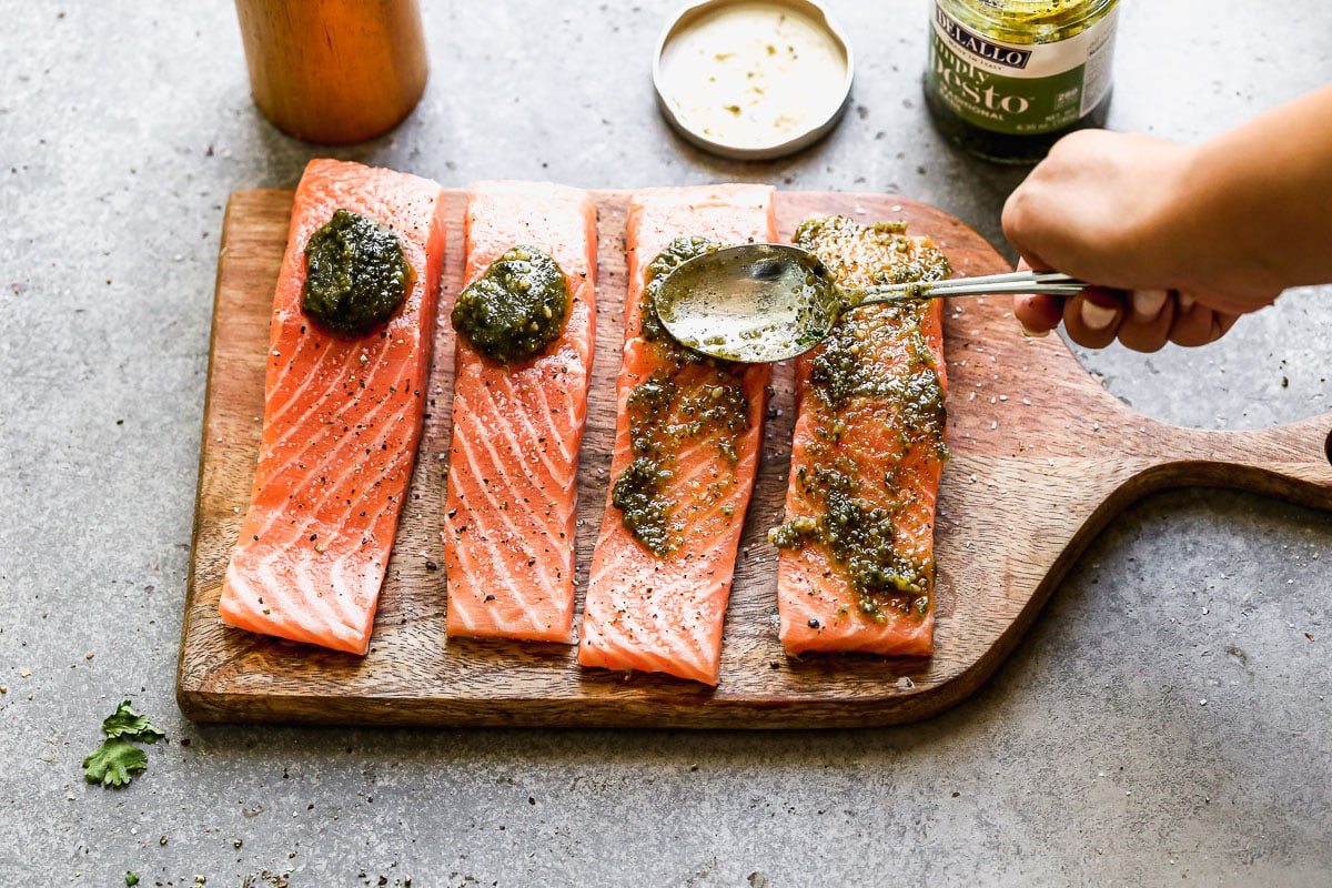 Pesto being spread on pieces of fish