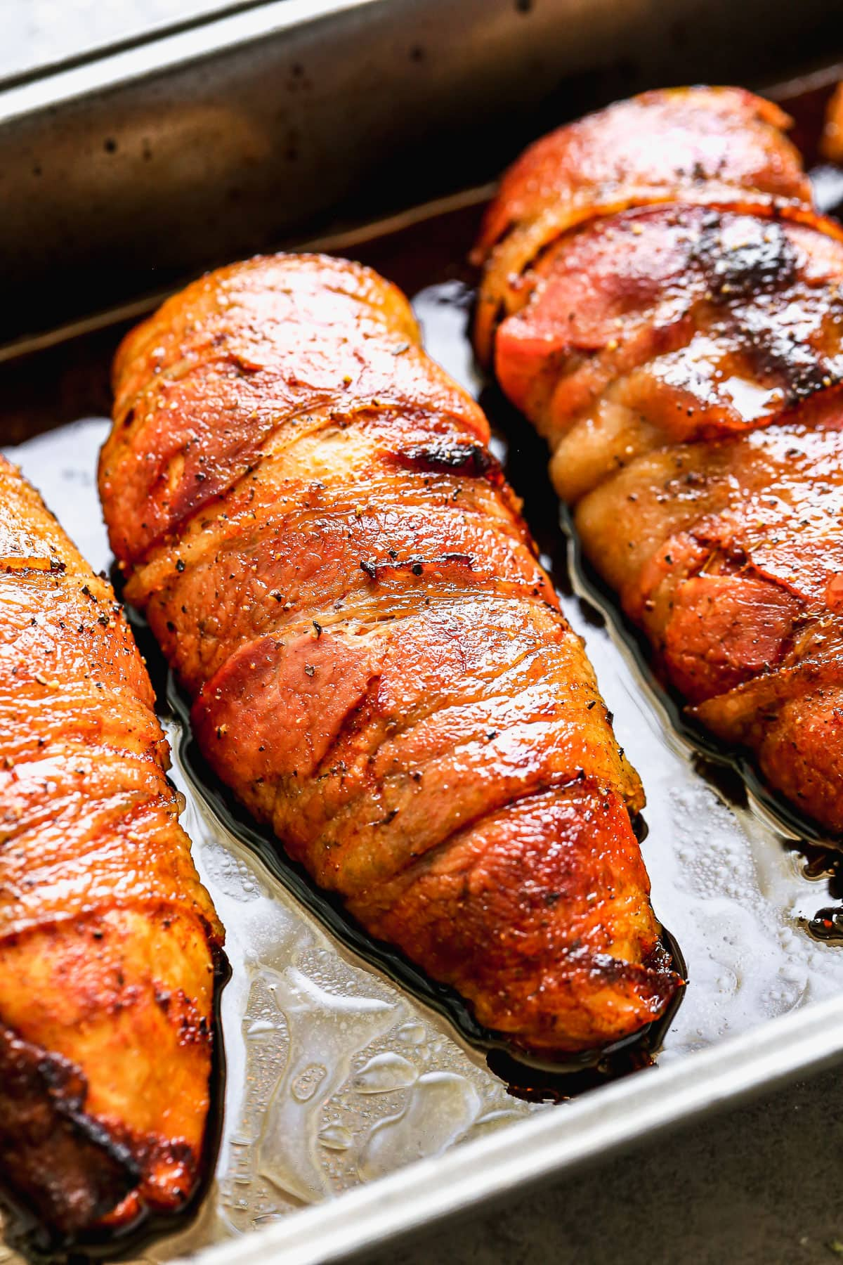 Bacon wrapped chicken breasts in a pan