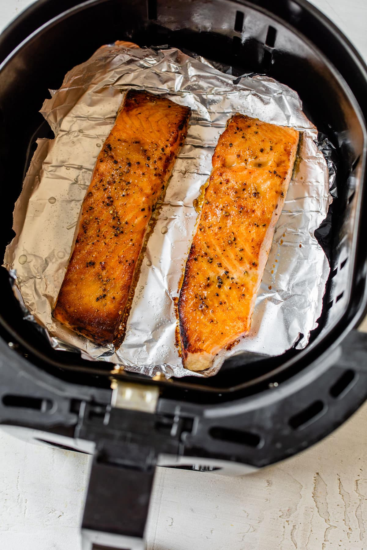 Two salmon fillets in an air fryer