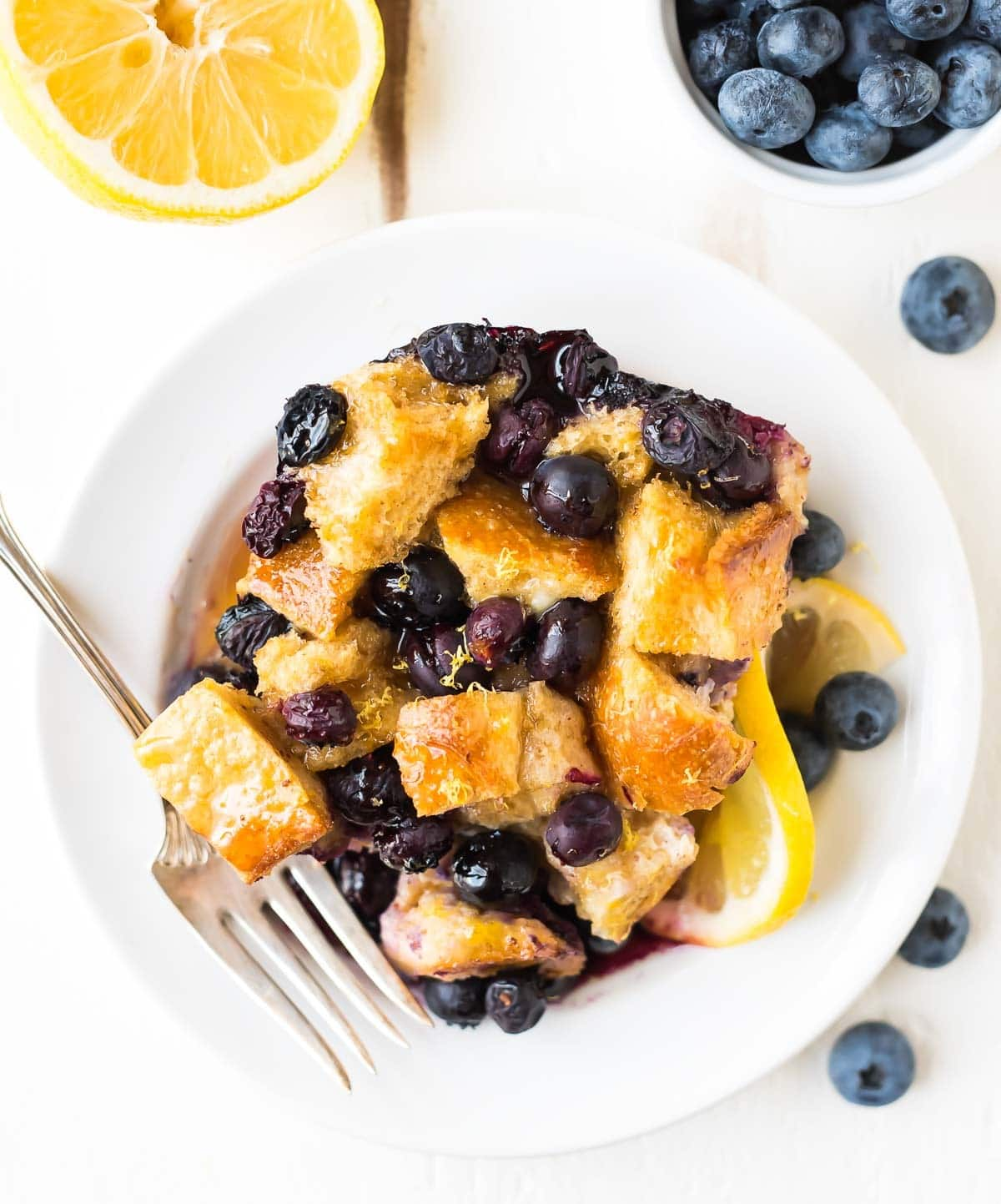 Blueberry French toast casserole in a bowl with lemons