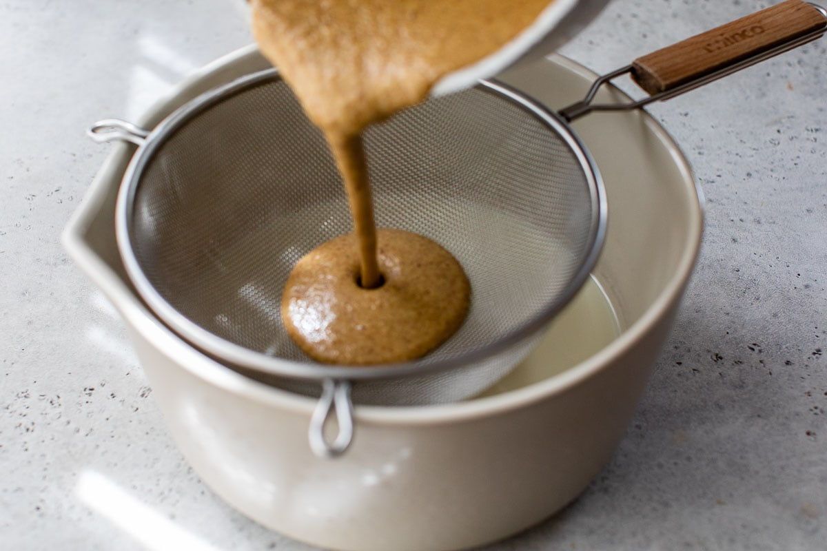 oatmilk ice cream batter being strained