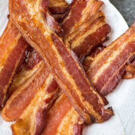 perfectly cooked slices of oven baked bacon on sheets of white paper toweling