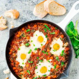 Italian Baked Eggs in Purgatory – Eggs baked in garlic tomato sauce with chickpeas, spinach, Parmesan, and fresh basil. Cheap, easy, and healthy! Also called eggs in purgatory or shakshuka, it's a crowd pleasing recipe that's perfect for brunch and quick dinners. Recipe at wellplated.com   @wellplated