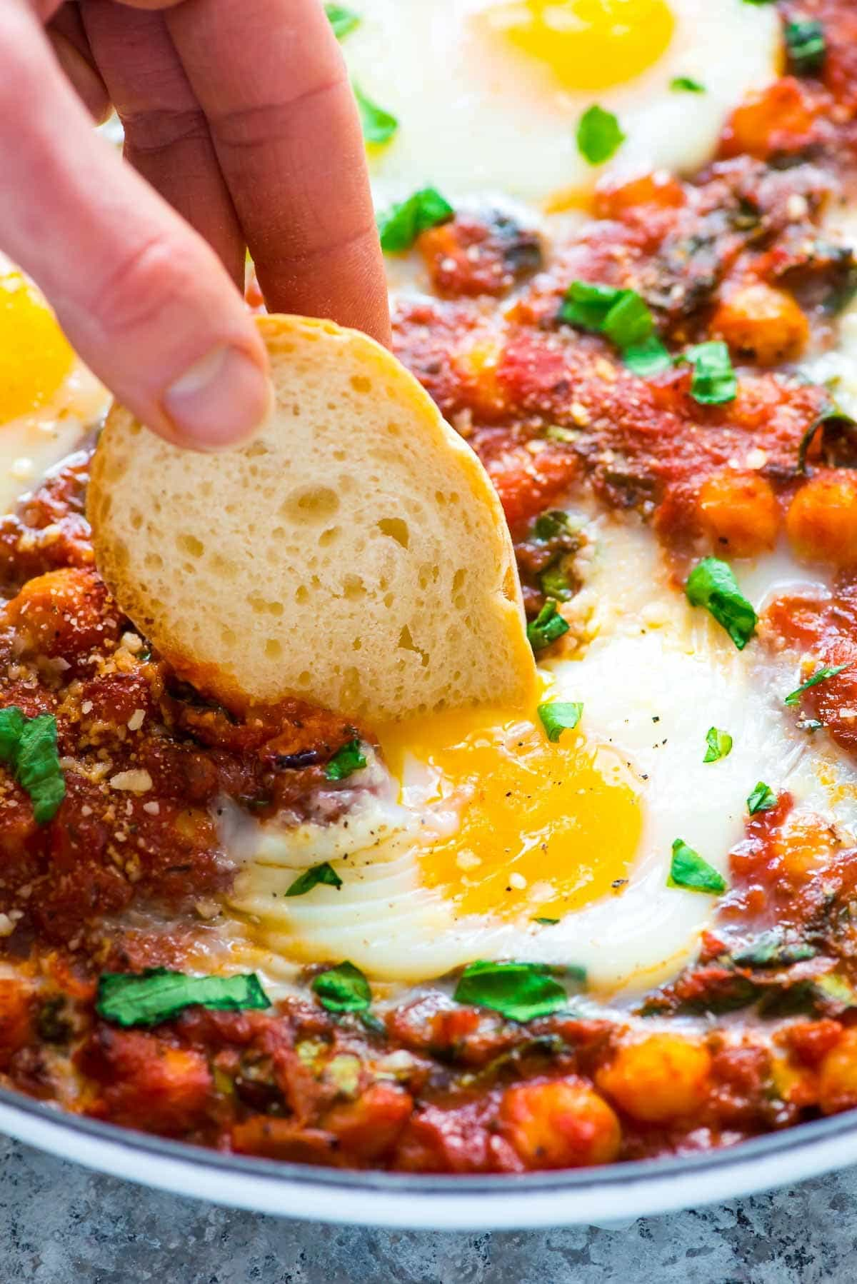 Italian Baked Eggs in Purgatory – Eggs simmered in a garlic tomato sauce with chickpeas, spinach, basil, and Parmesan. Easy, healthy, budget-friendly, and DELICIOUS! Recipe at wellplated.com   @wellplated