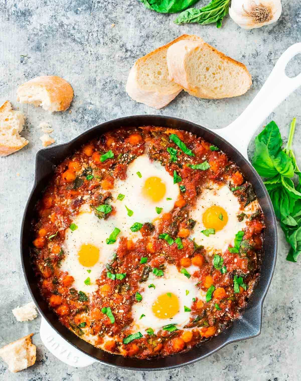 Italian Baked Eggs in Purgatory – Eggs baked in garlic tomato sauce with chickpeas, spinach, Parmesan, and fresh basil.