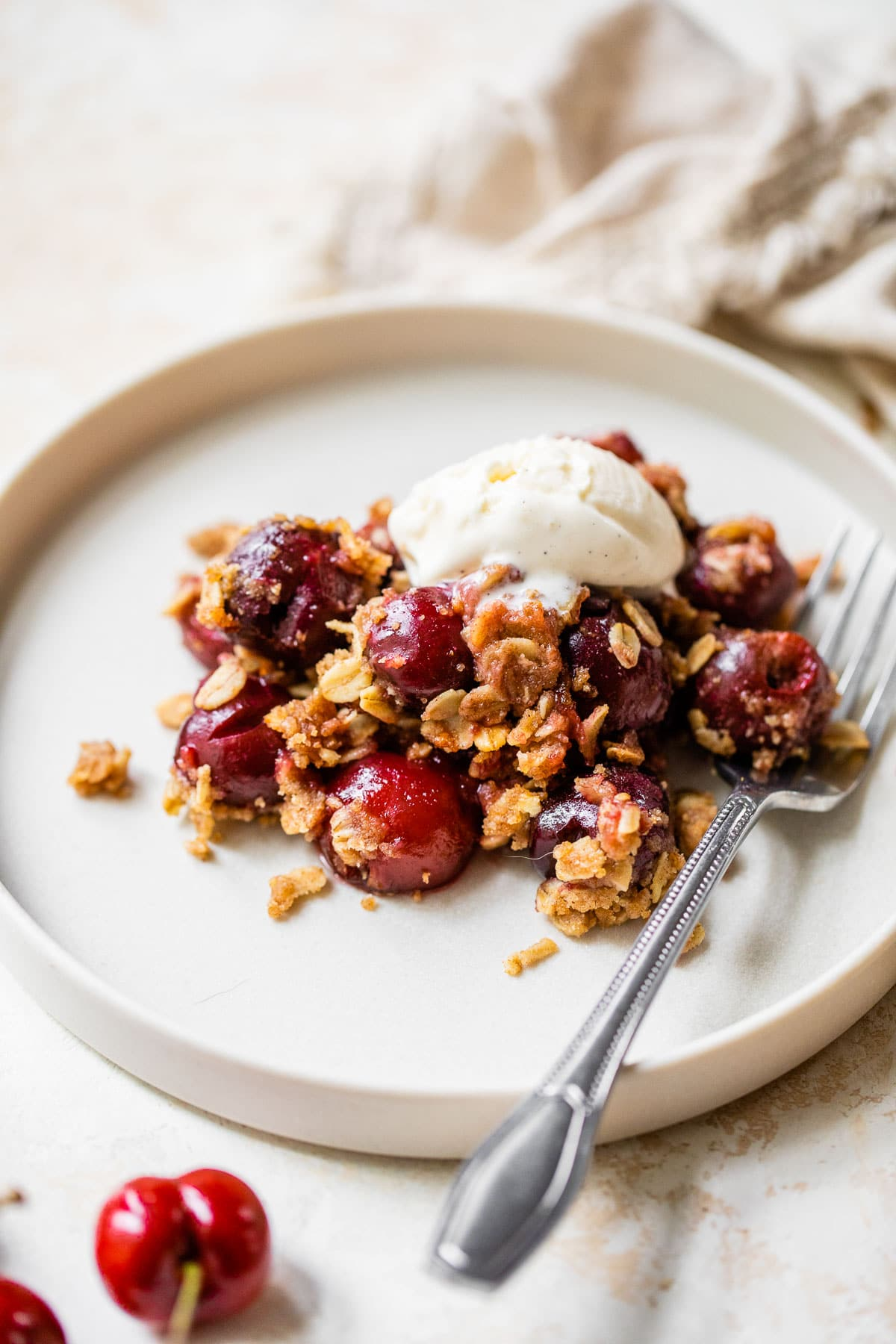 Freshly baked old-fashioned cherry crisp on a plate with a spoon and vanilla ice cream melting on top