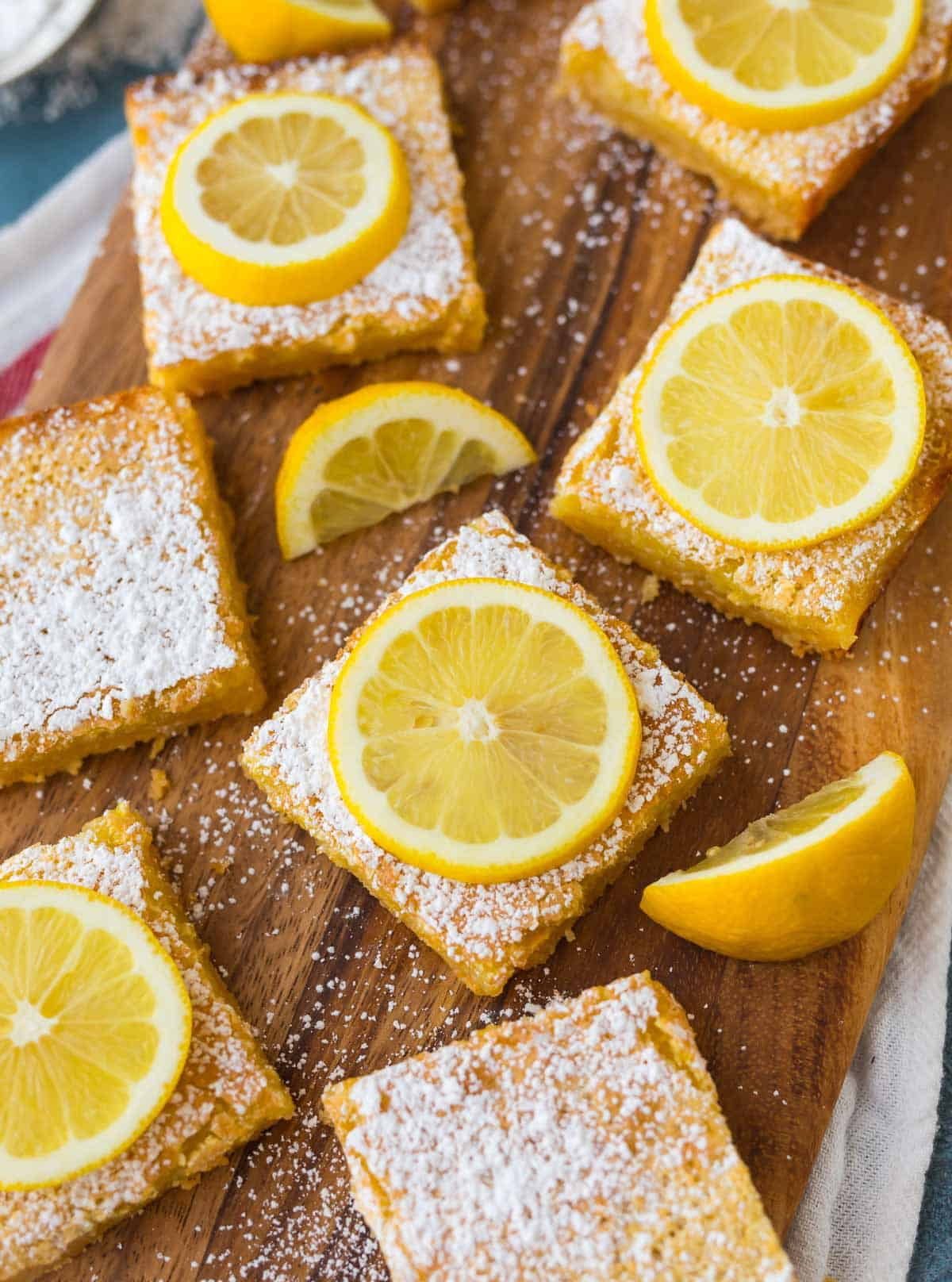 Close-up photo of lemon bars cut into squares on a butcher block board with powdered sugar and lemon slices