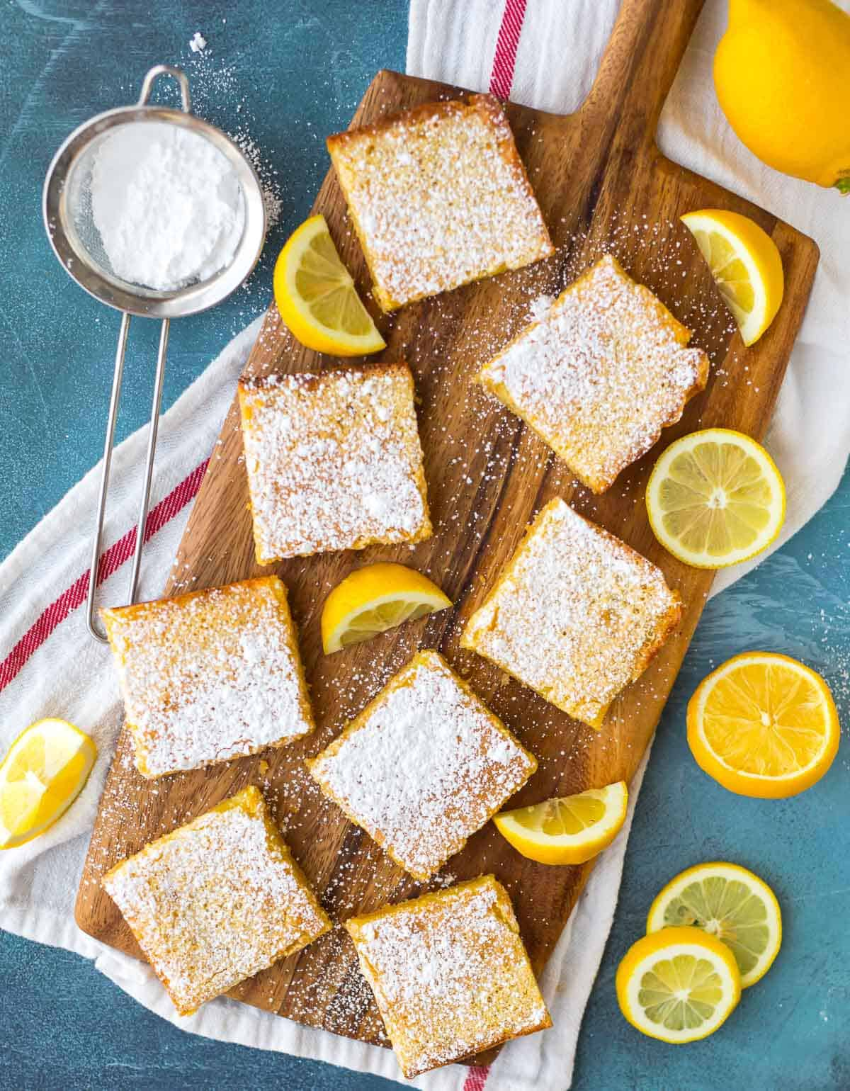 Homemade lemon bars dusted with powdered sugar on a wood serving board with lemon slices and wedges