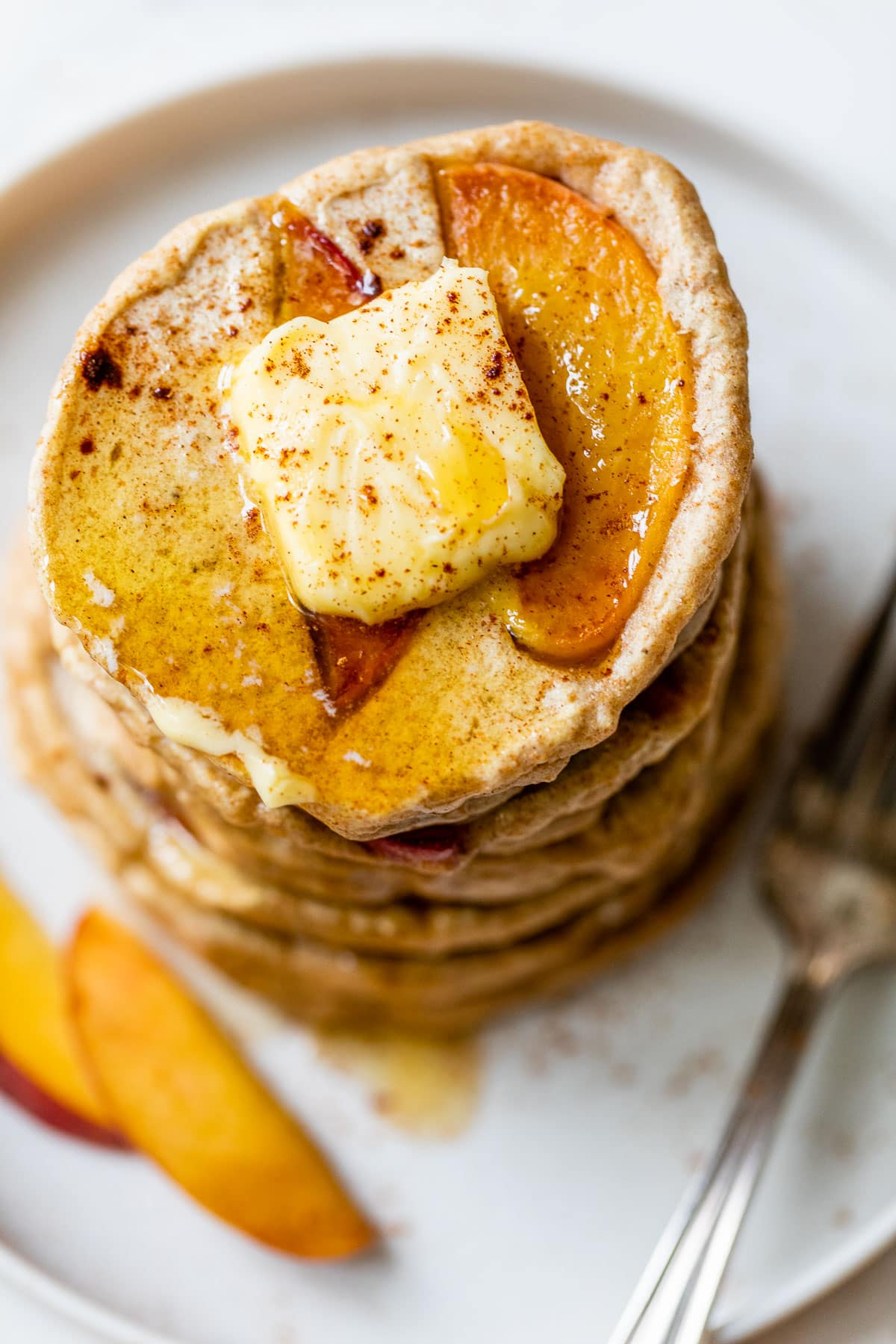 healthy pancakes with caramelized peaches in a stack