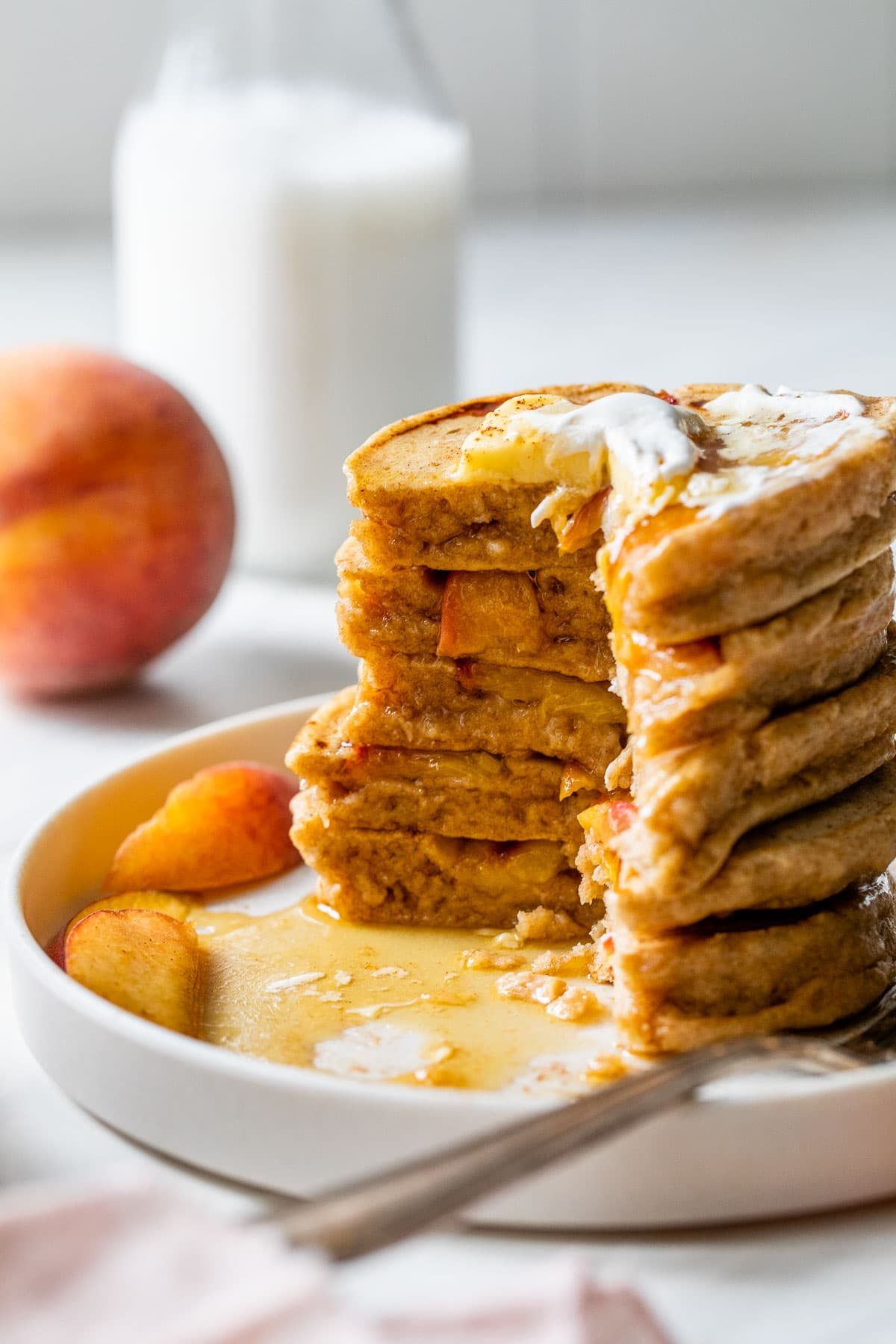 caramelized peach pancakes with a bite cut out