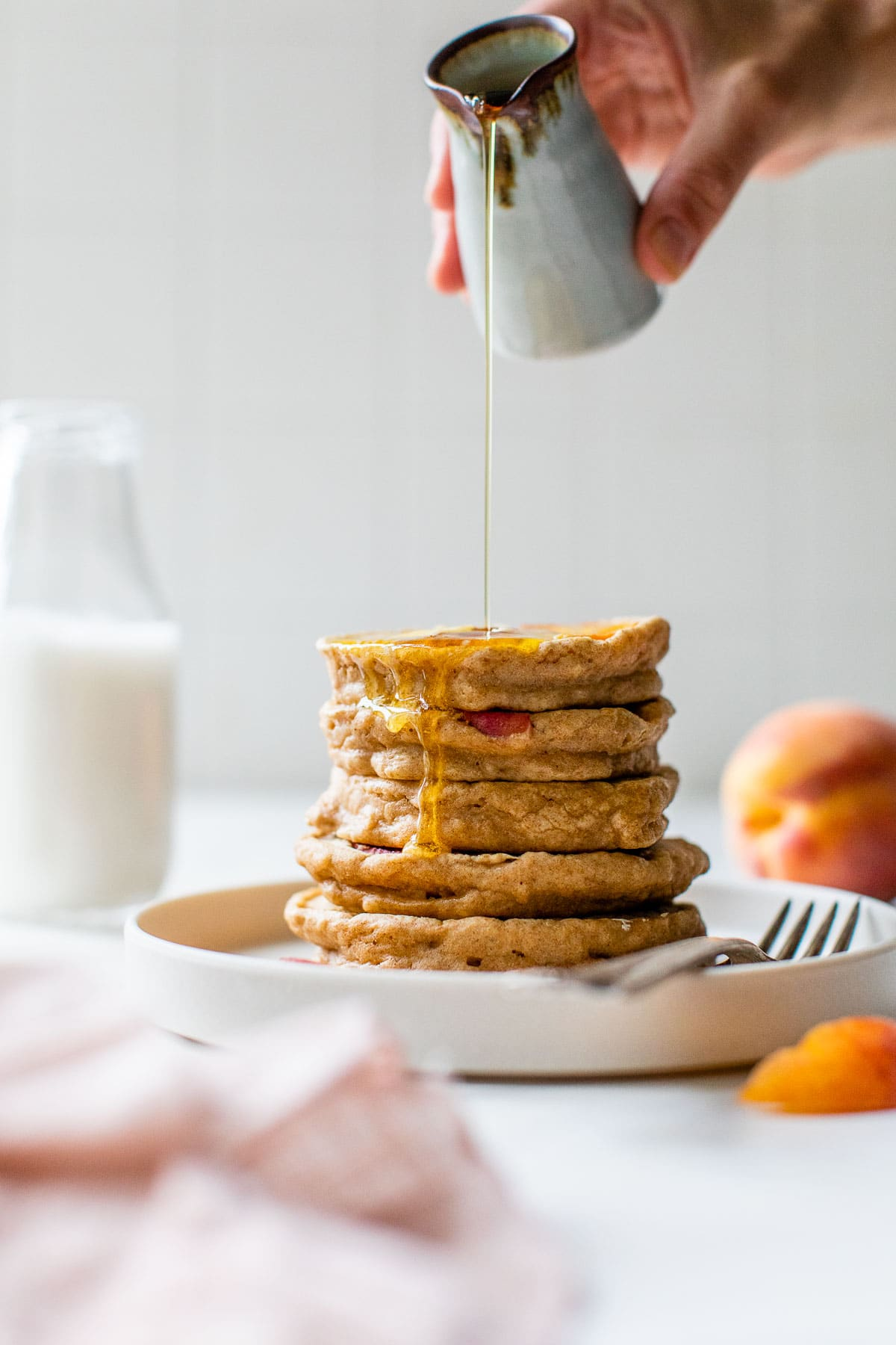 Syrup pouring onto a stack of fresh peach pancakes