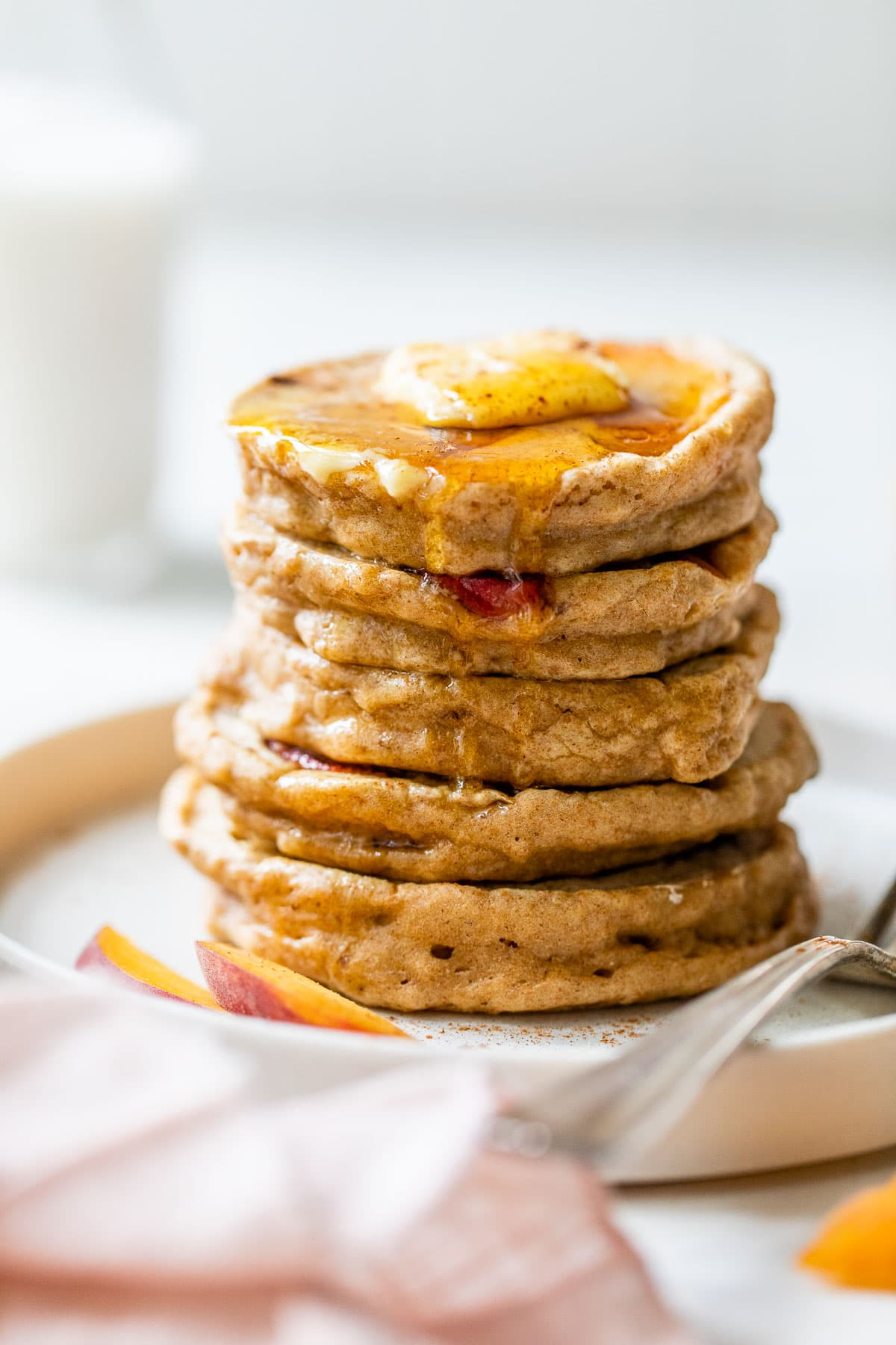 a stack of fluffy fresh peach pancakes with syrup