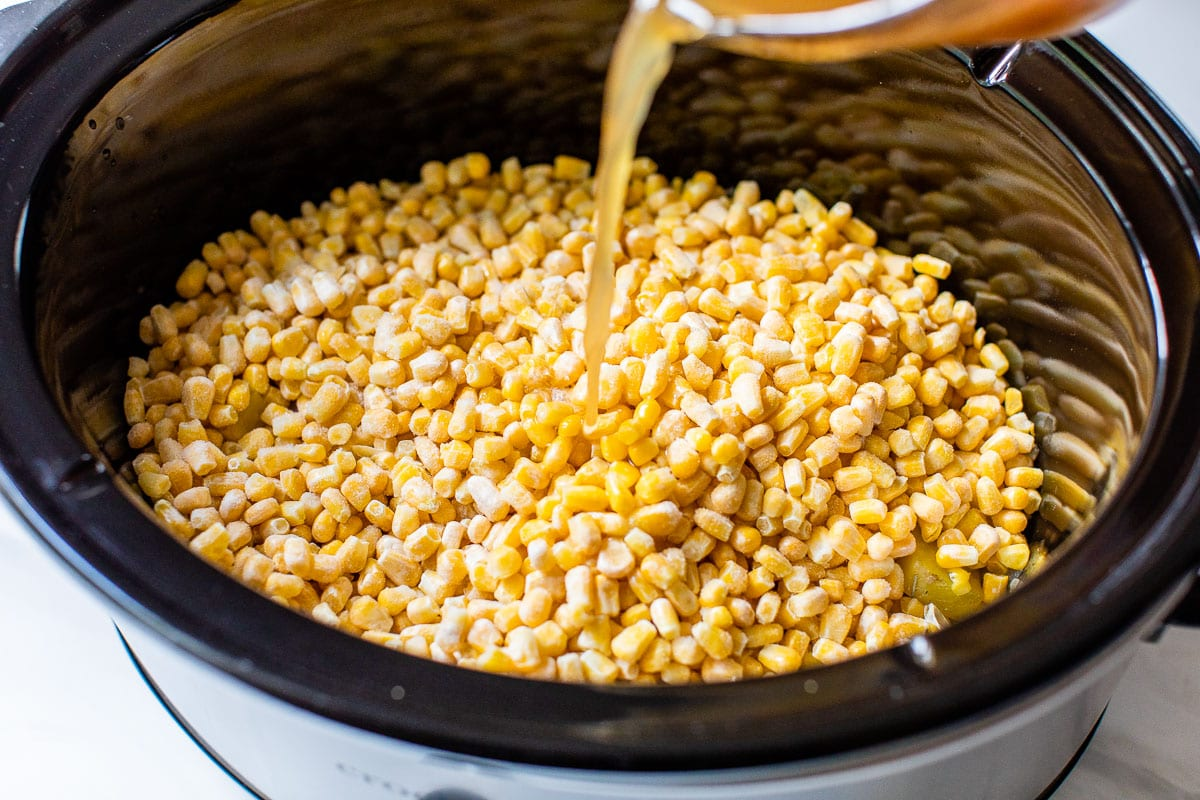 pouring chicken stock in slow cooker with corn