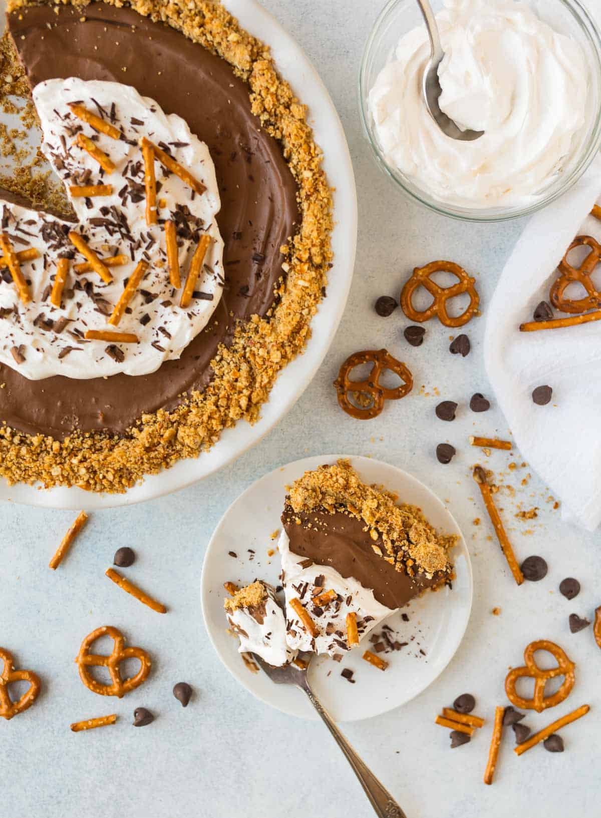 Easy Vegan Chocolate Mousse Pie surrounded by a bowl of vegan whipped cream, pretzels and chocolate chips