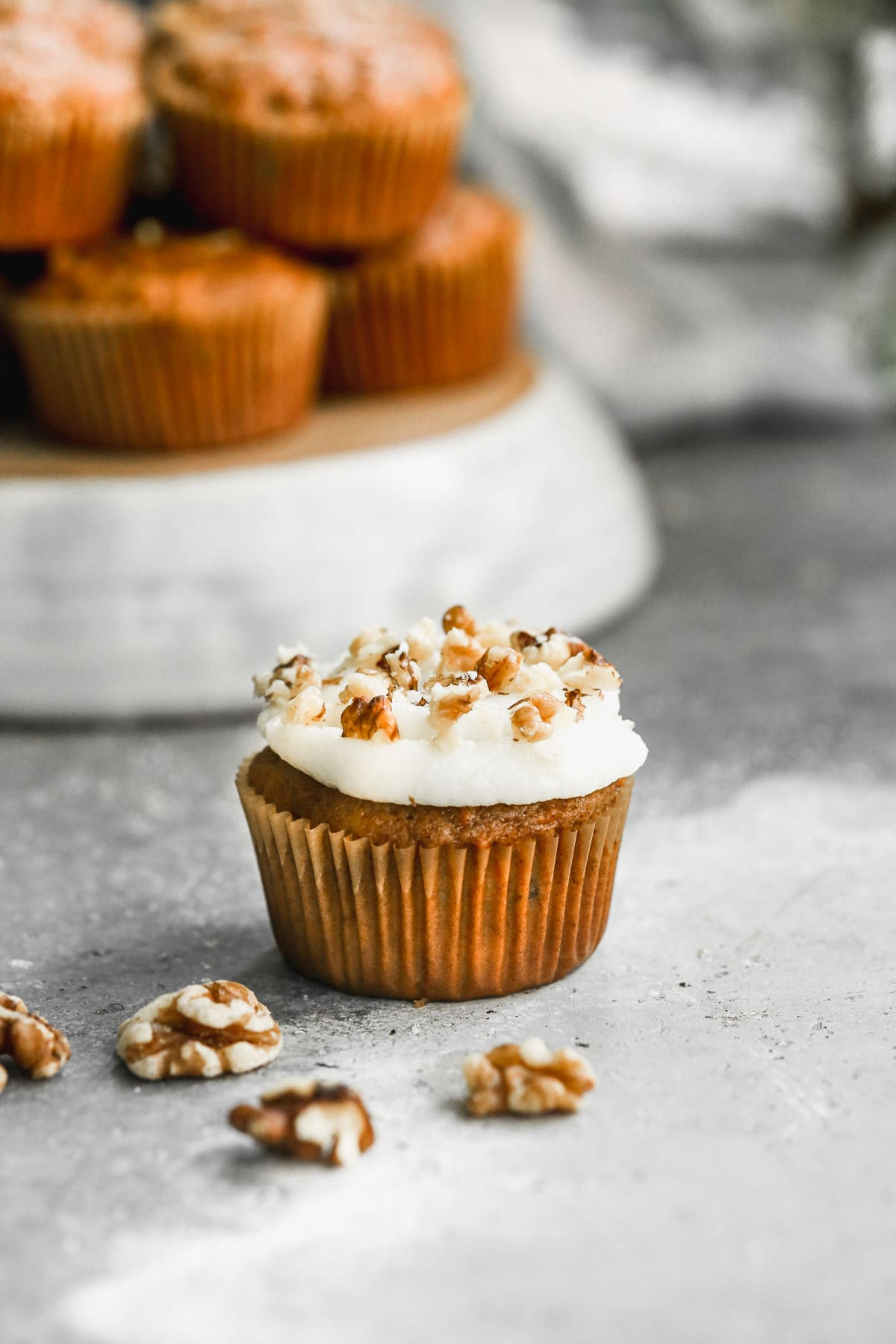 A fluffy carrot cake cupcake with cream cheese frosting and sprinkled with nuts