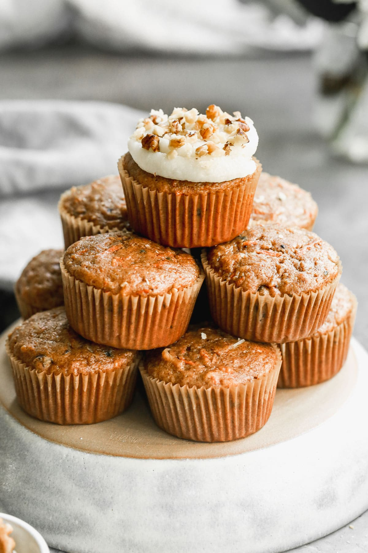 a stack of loaded carrot cake cupcakes the top cupcake is frosted with homemade cream cheese icing and chopped walnuts