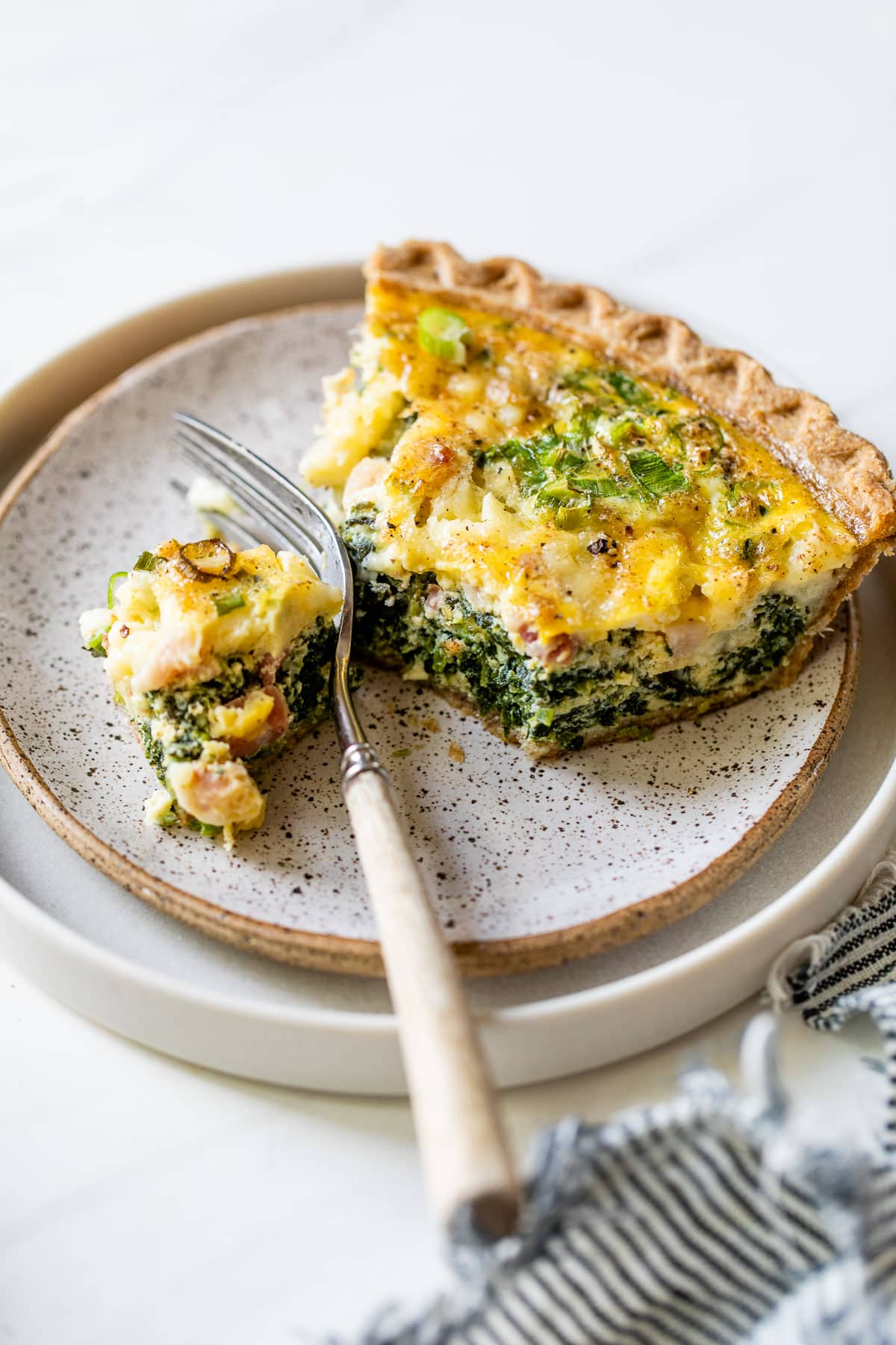 a slice of easy spinach quiche on a plate with a fork