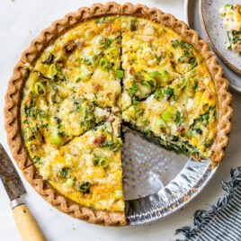 Easy quiche with spinach, cheese, and ham in a store bought pie crust with a slice cut out