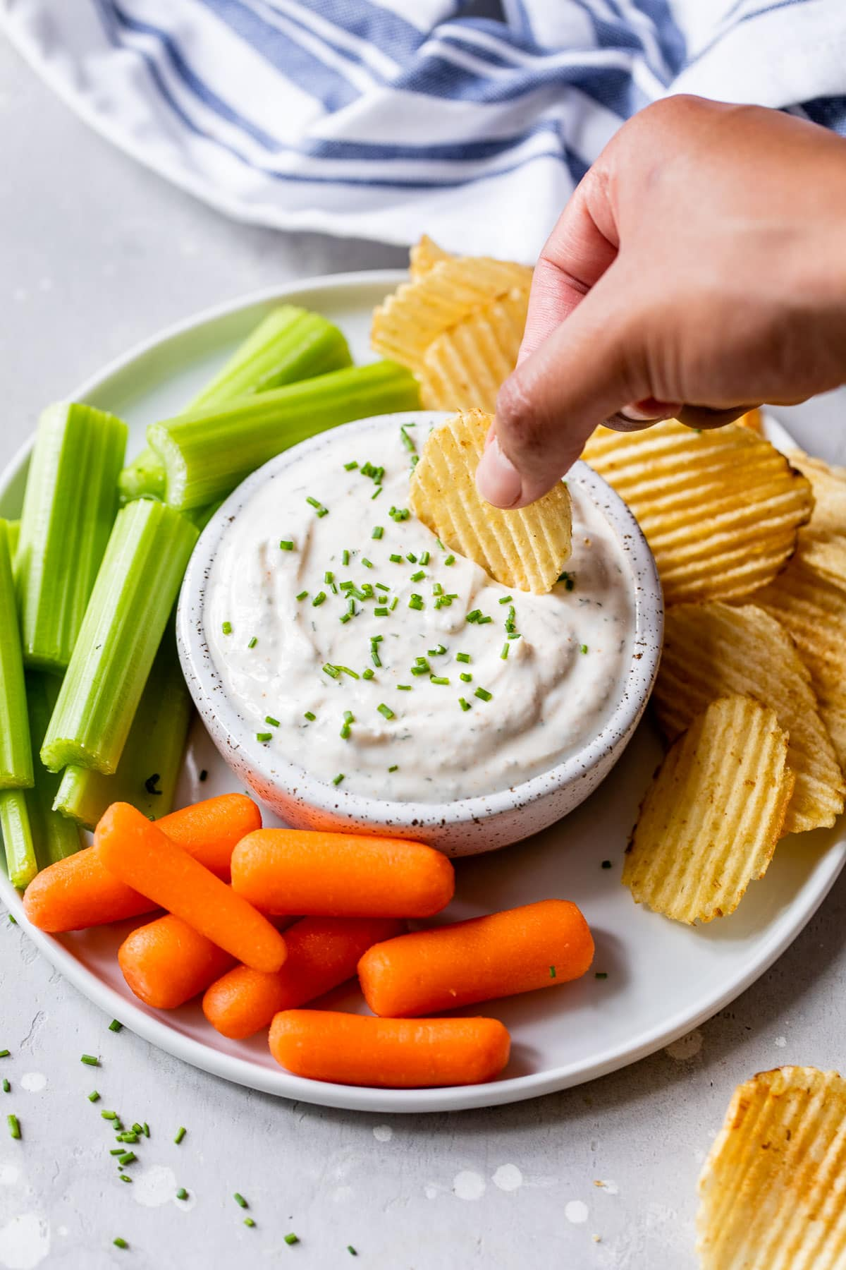 a chip being dipped into guilt-free greek yogurt ranch dip on a platter with vegetables