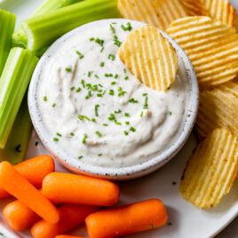 A white bowl of Greek yogurt ranch dip with carrots and celery on the side and a chip in the dip