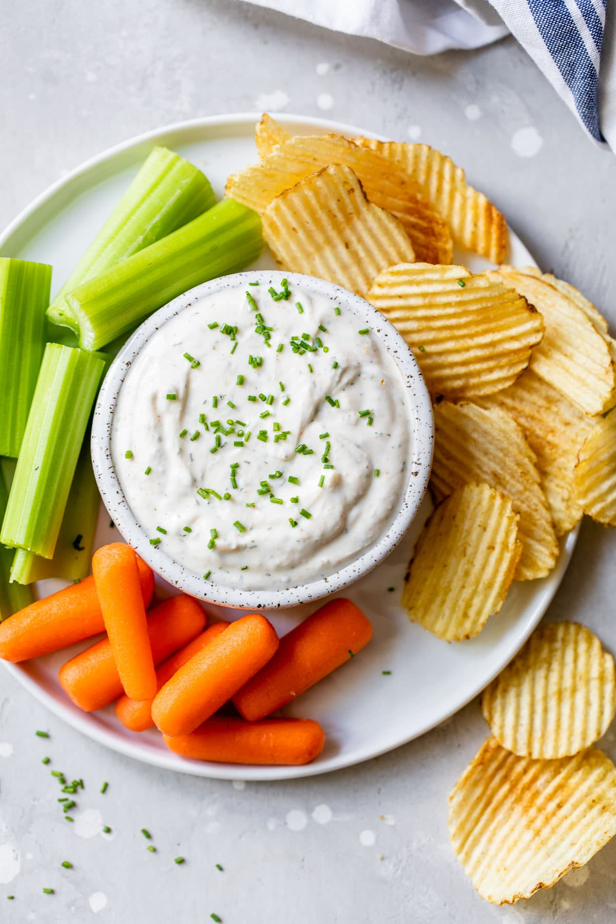 a white bowl filled with greek yogurt ranch dip surrounded by chips and veggies