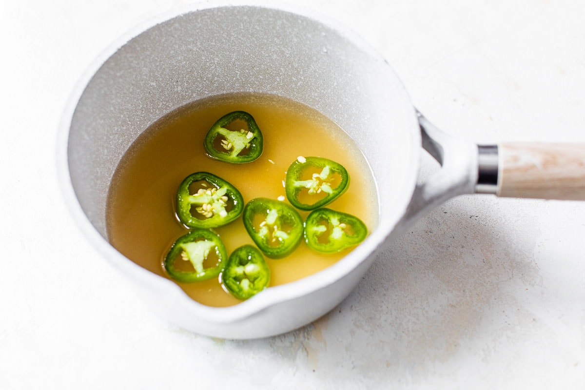 jalapenos and peach syrup in a saucepan