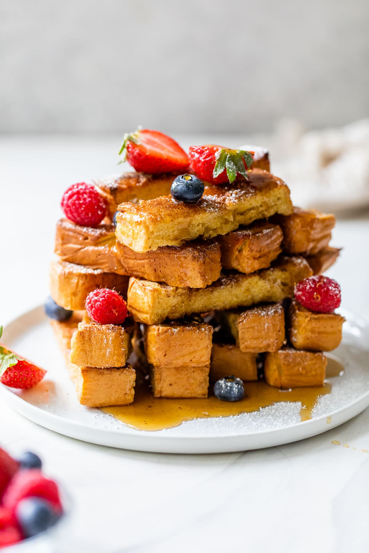 oven baked french toast sticks on a plate with powdered sugar