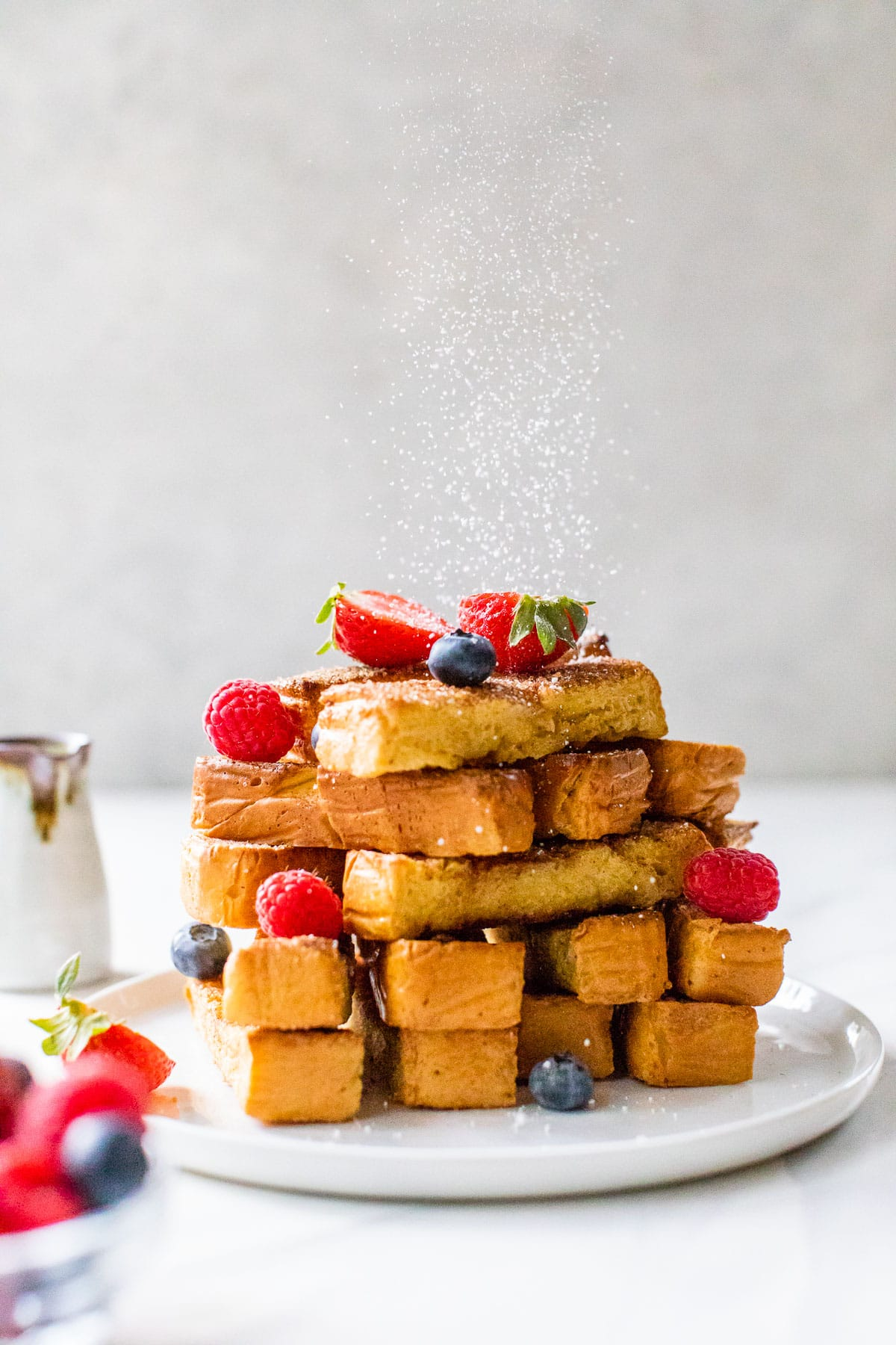 crispy french toast sticks stacked on a plate
