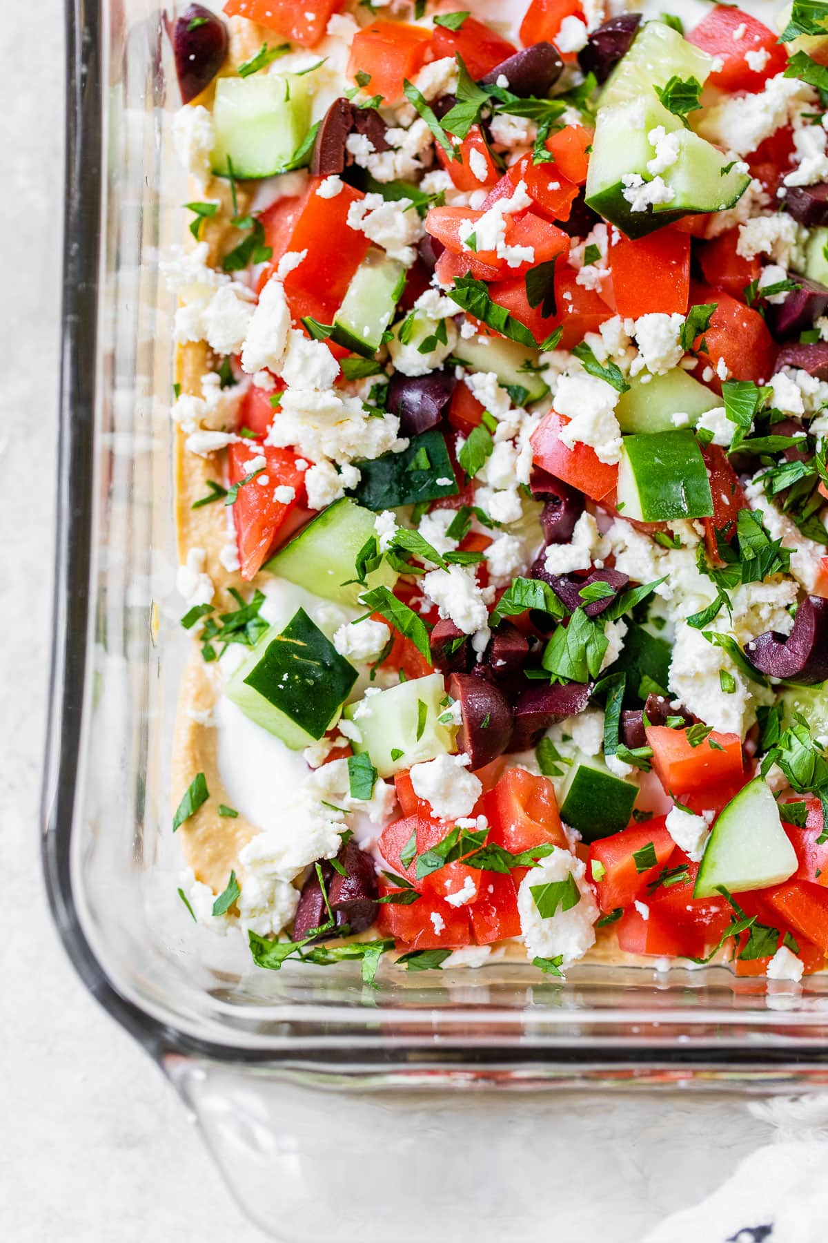 Skinny Greek Layer Dip made with hummus in a glass dish