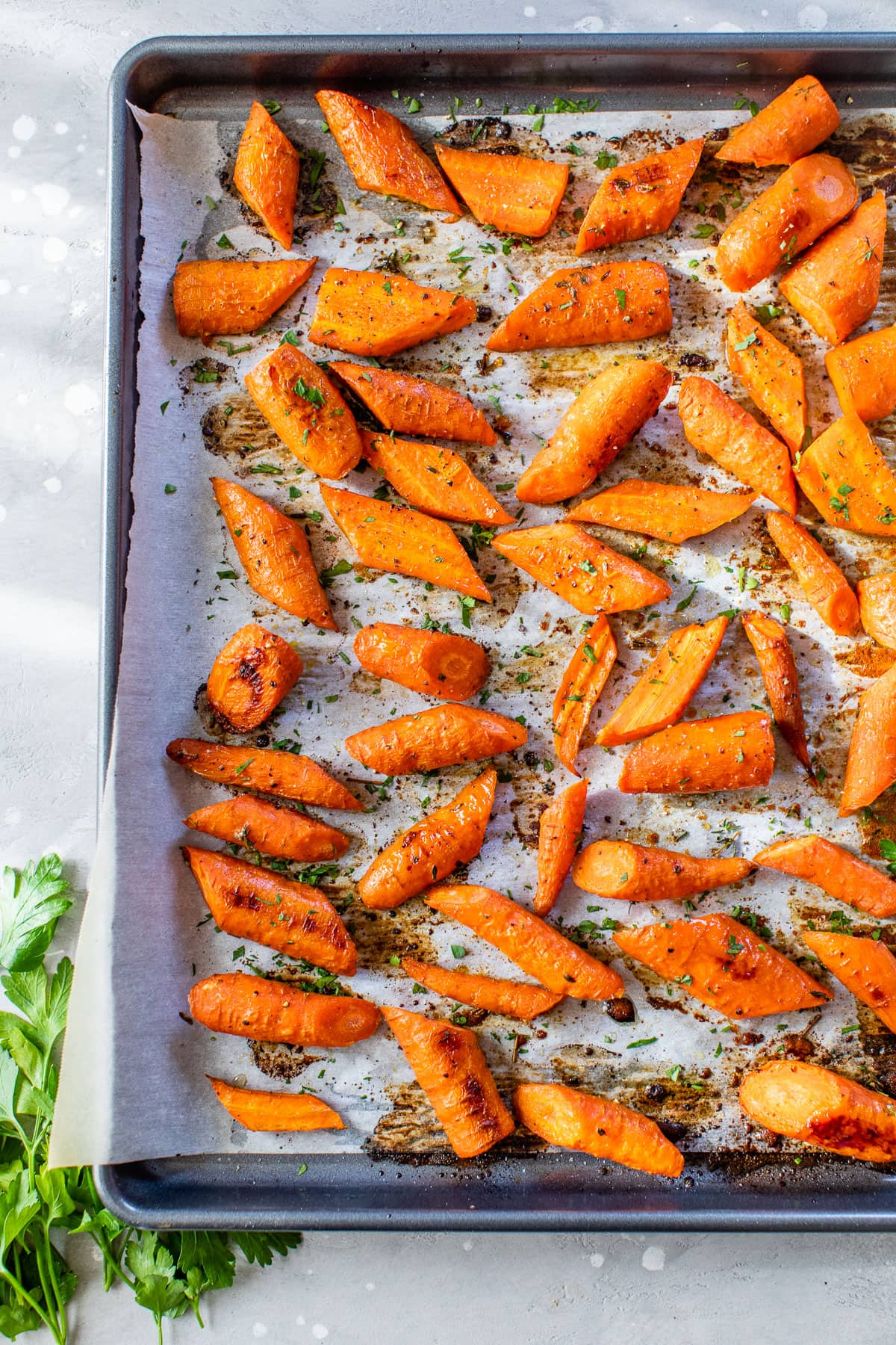 a sheetpan with roasted carrots sprinkled with herbs