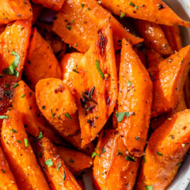 a white bowl with herb honey roasted carrots