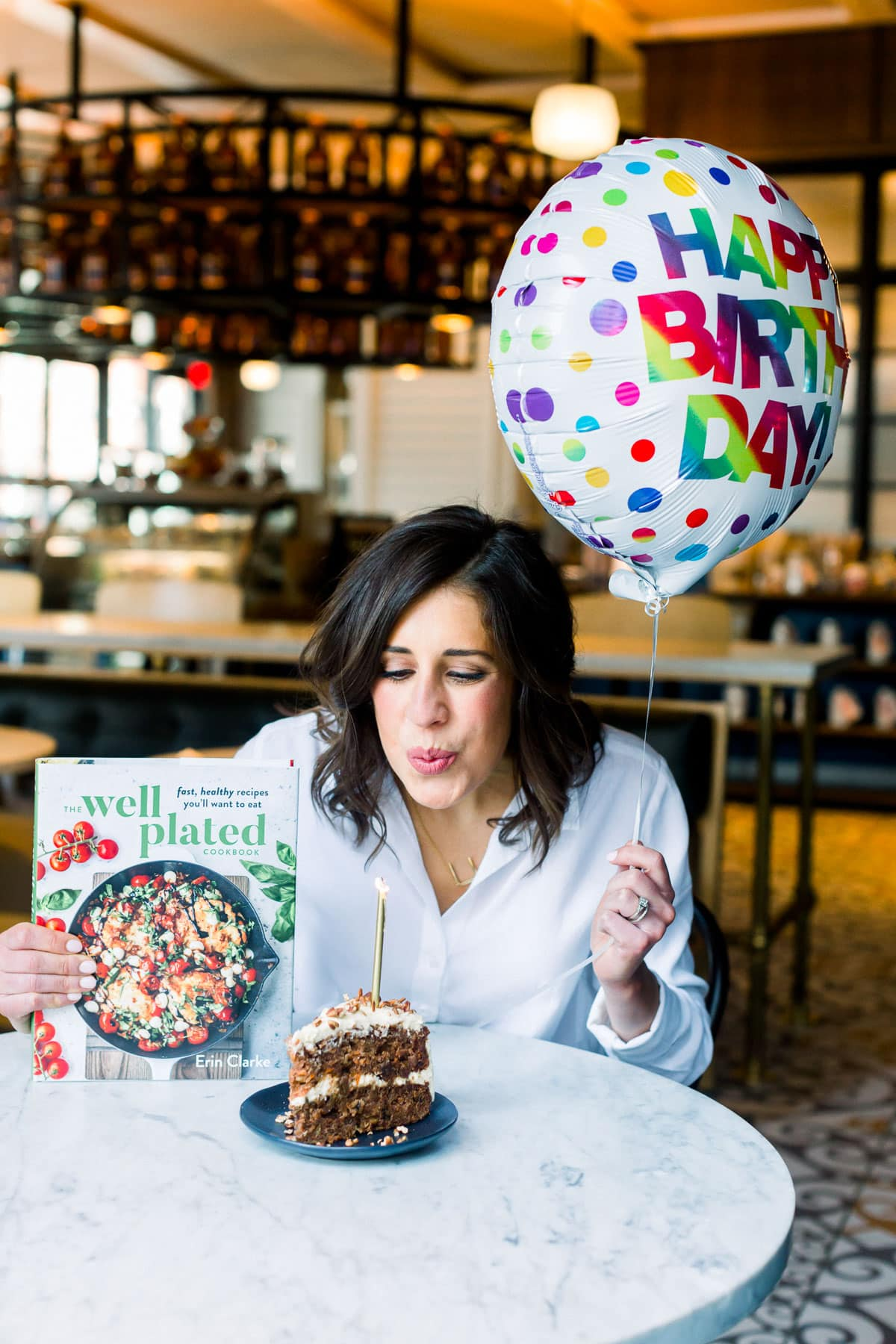 Erin Clarke blowing out a candle with a copy of The Well Plated Cookbook and a birthday balloon