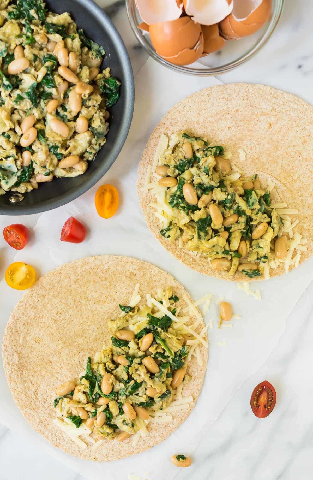 Filling wheat tortillas with scrambled eggs, spinach, cheese and white beans for breakfast quesadillas