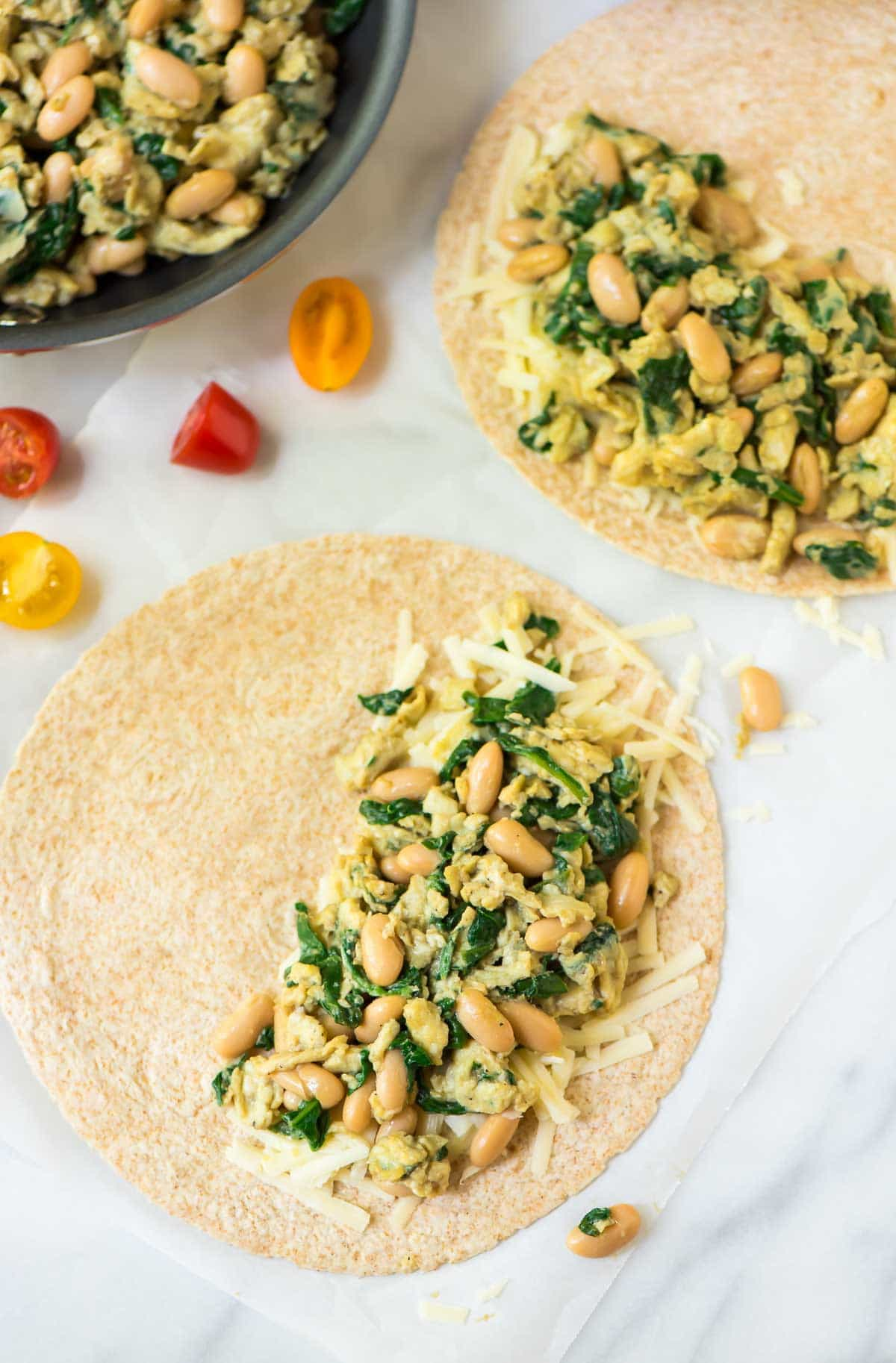 Wheat tortillas filled with eggs, white beans, spinach and cheese sitting on parchment paper
