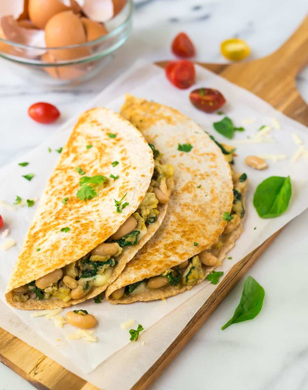 Make Ahead Freezer Breakfast Quesadilla with eggs, spinach, cheese, and white beans sitting on parchment paper and a cutting board