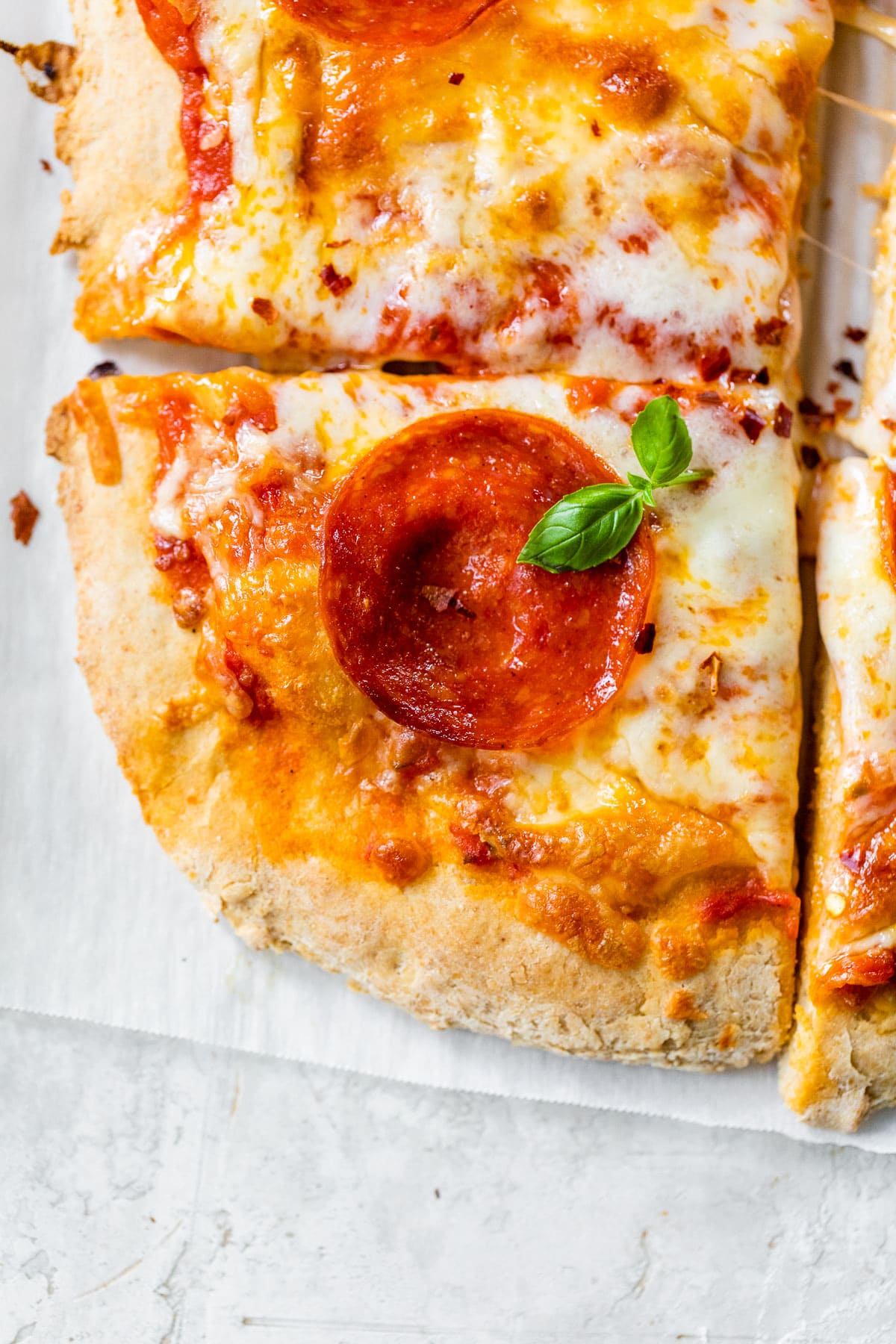 a pepperoni pizza made with whole wheat pizza crust sliced on parchment paper