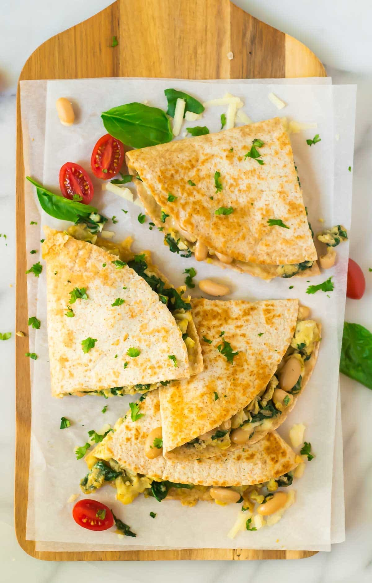 Freezer Breakfast Quesadilla with eggs, spinach, cheese, and beans on a wood serving board and parchment paper