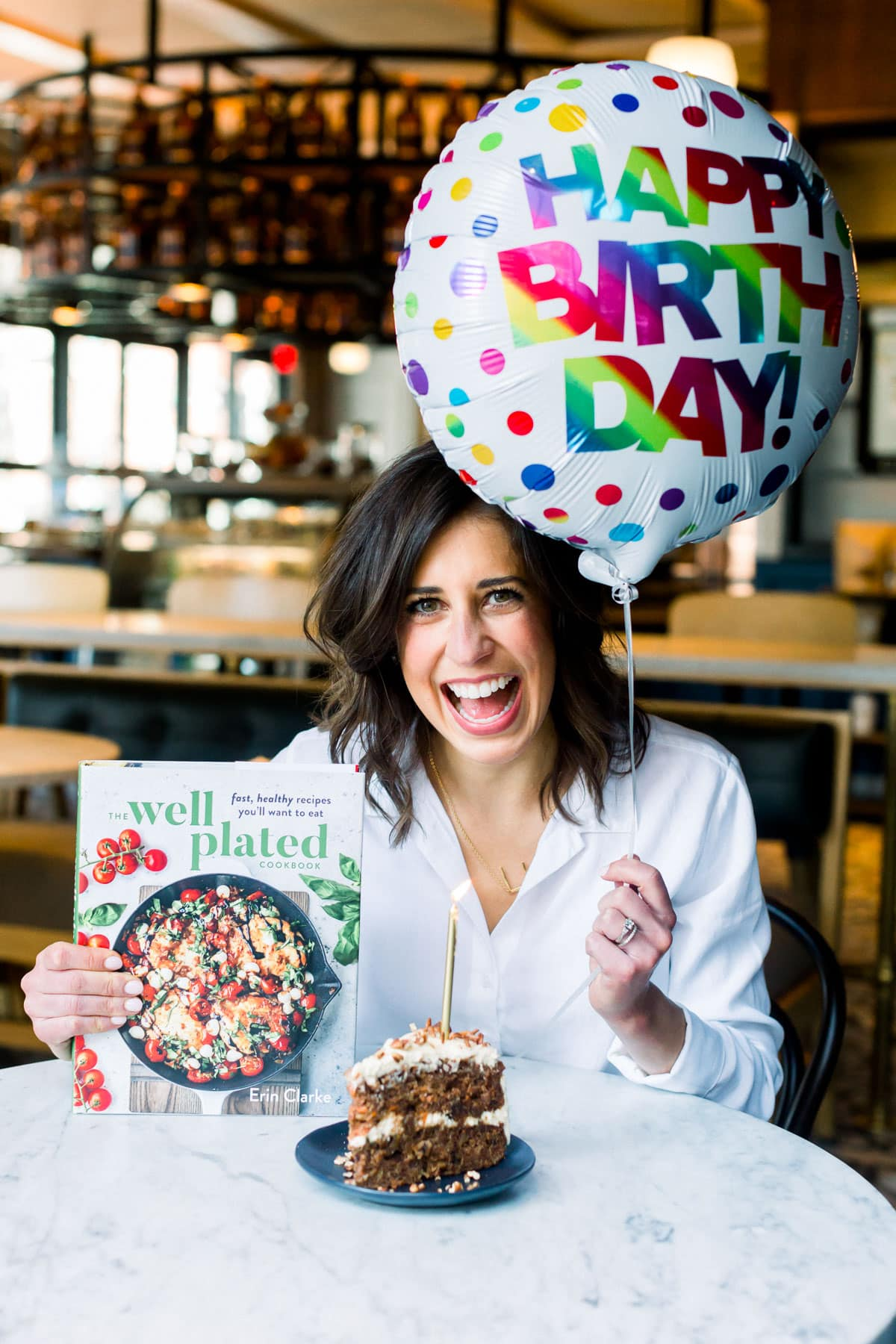 Erin Clarke with a slice of cake, birthday balloon, and copy of The Well Plated Cookbook