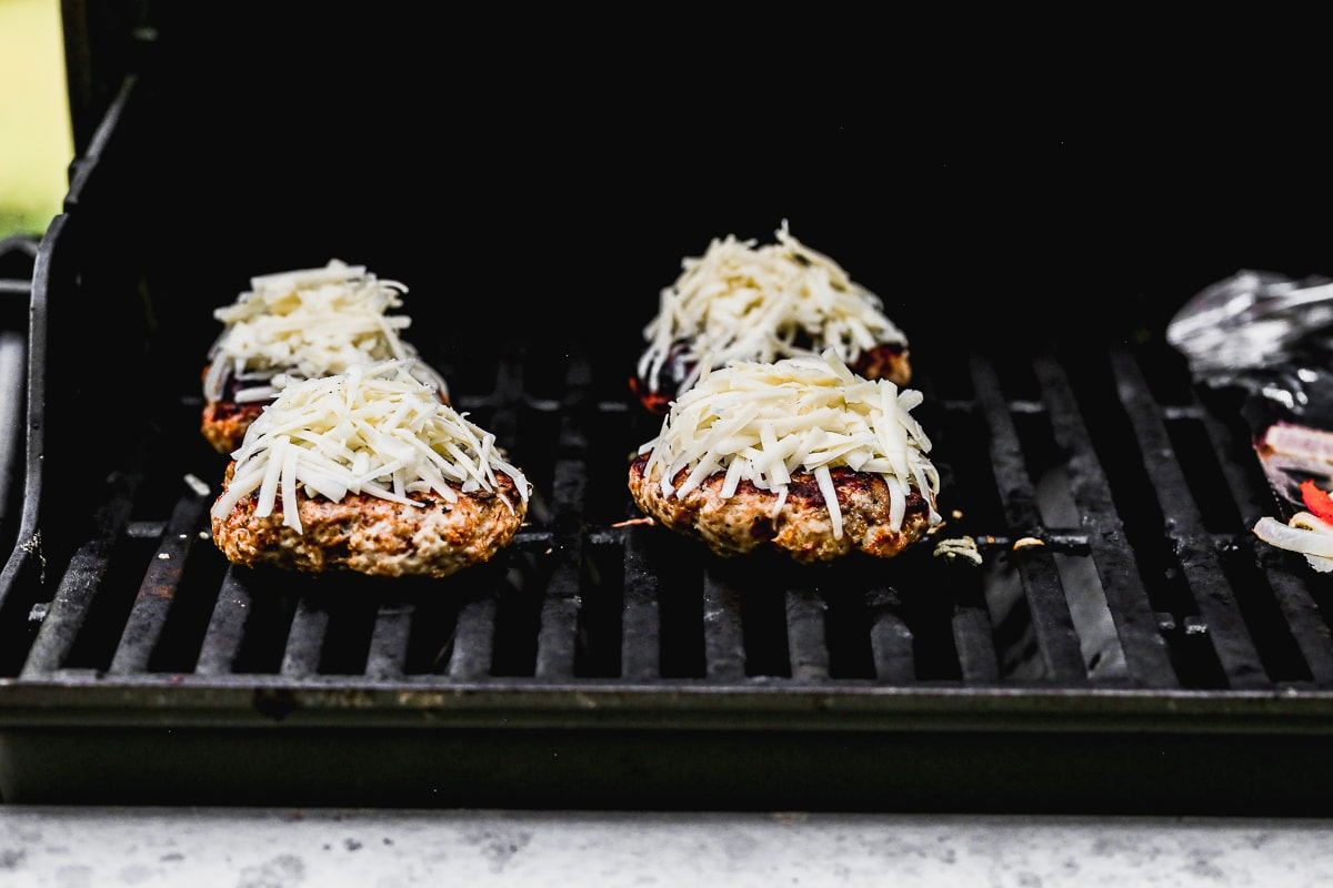 topping italian turkey burger patties with shredded cheese on a hot grill