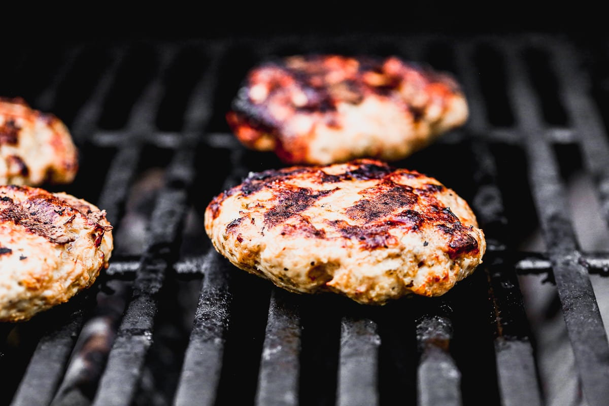 juicy italian turkey burger patties on a hot grill with charred grill marks