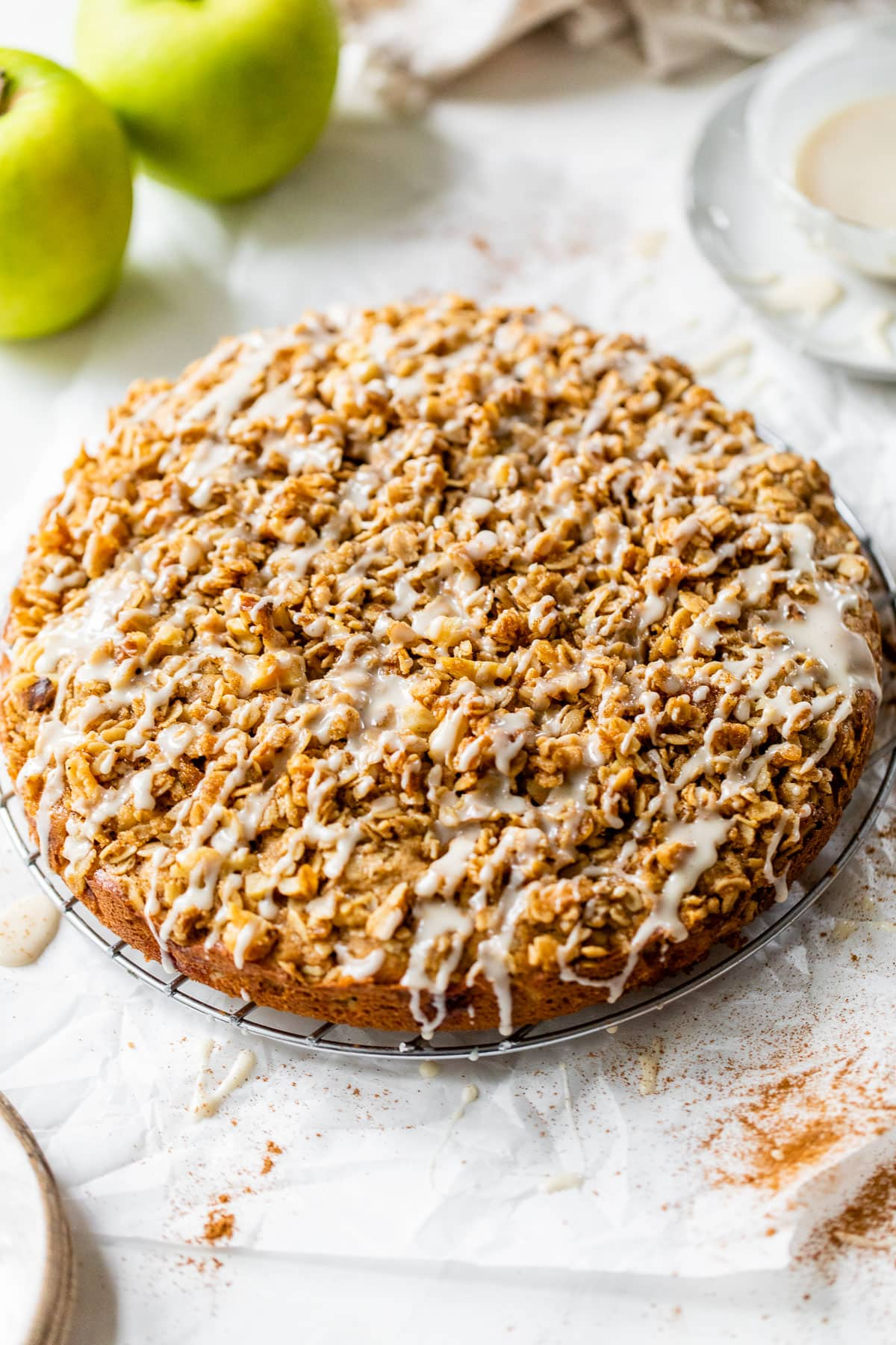 Apple Coffee Cake with Cinnamon Streusel Topping on a cake plate topped with glaze