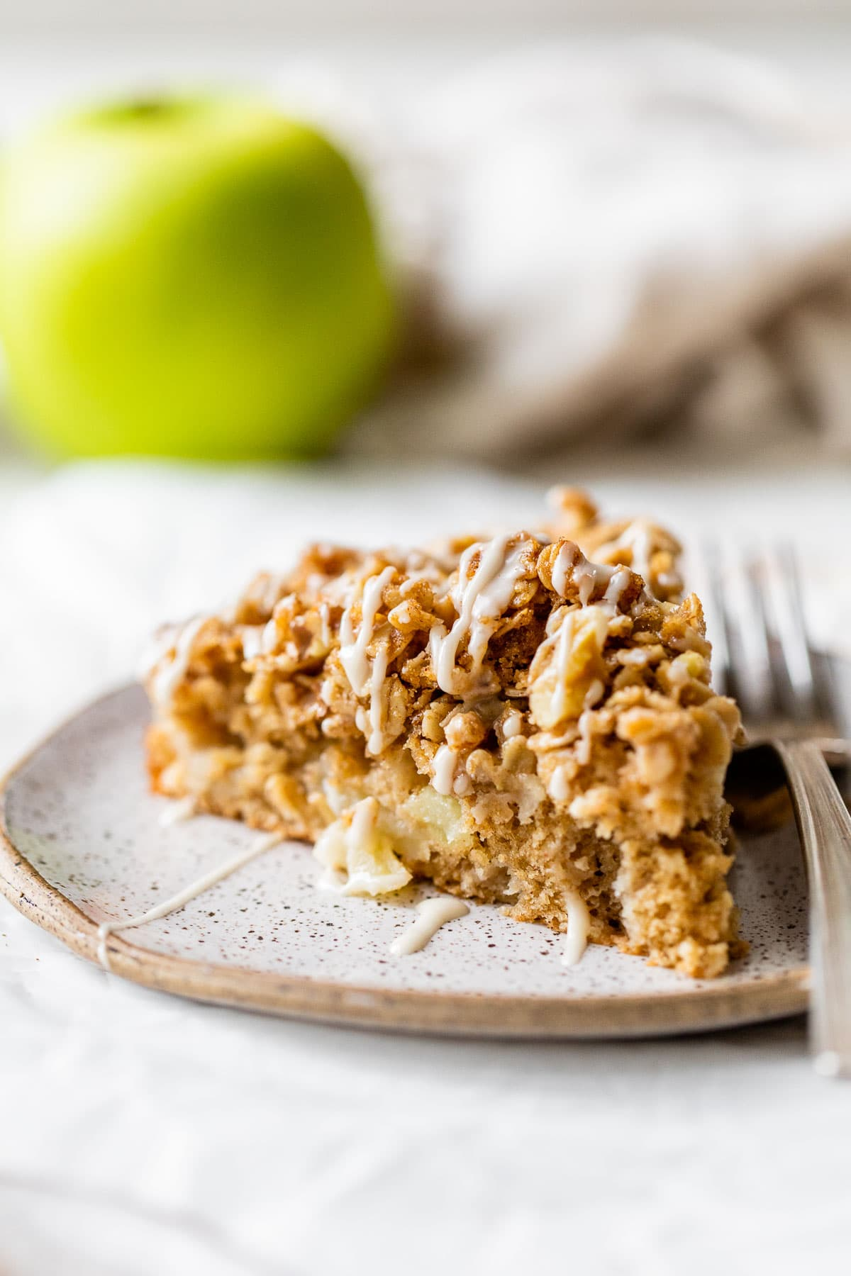 a slice of healthy apple coffee cake on a plate with a fork