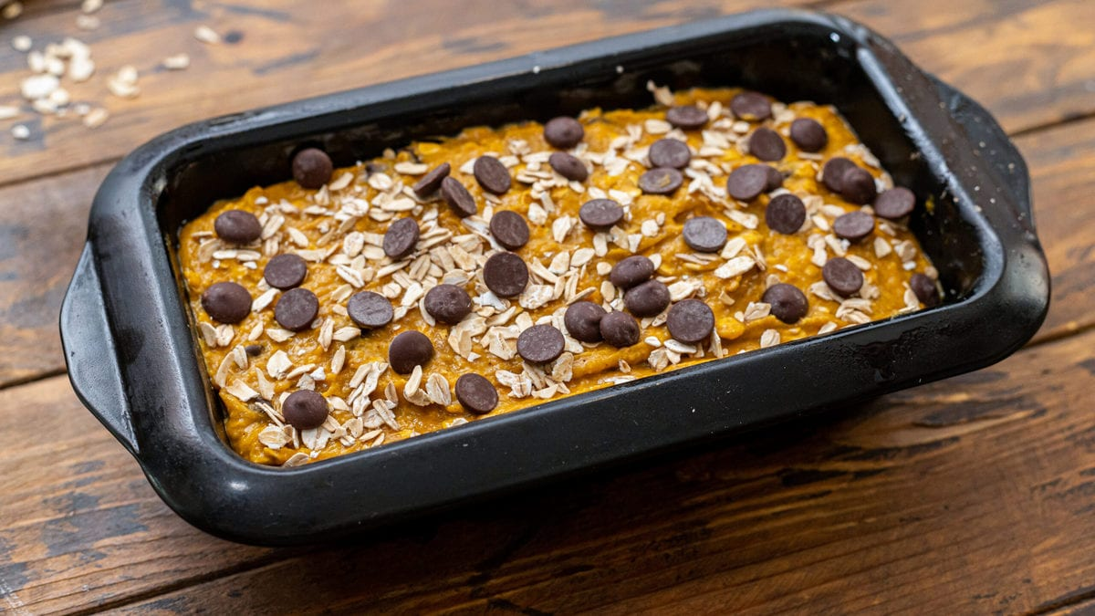 Pumpkin bread batter in a loaf pan and topped with oats and chocolate chips