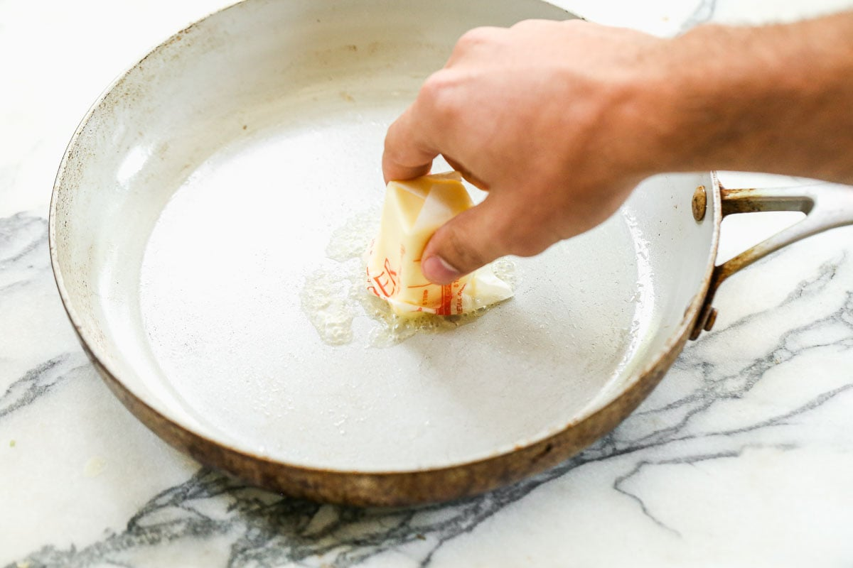 Butter being added to a skillet