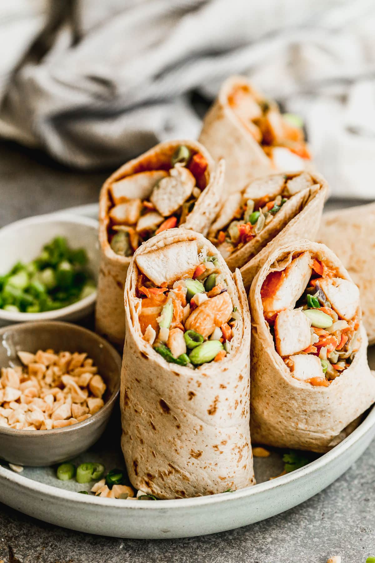 a plate of asian chicken wraps with thai peanut sauce and crunchy peanuts