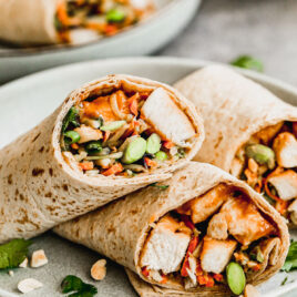 An Asian Chicken Wraps with Thai Peanut Sauce cut in half on a plate with peanuts