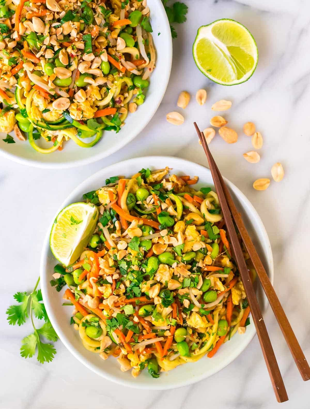 Two bowls of 30-minute vegetarian Pad Thai with Zoodles garnished with lime wedges and peanuts